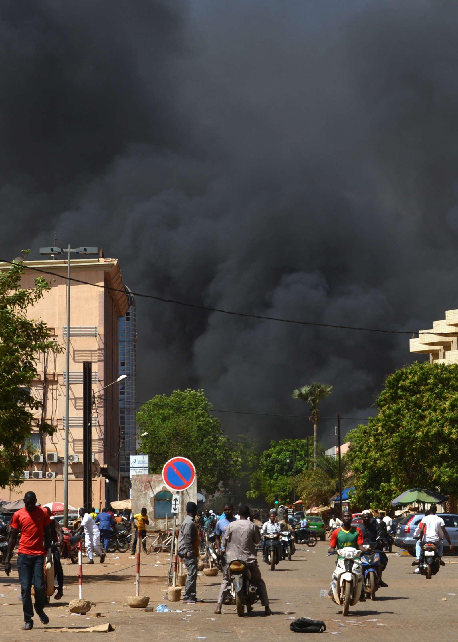 People watch as black smoke rises as the capital of Burkina Faso came under multiple attacks on March 2, 2018, targeting the French embassy, the French cultural centre and the country's military headquarters. Witnesses said five armed men got out of a car and opened fire on passersby before heading towards the embassy, in the centre of the city. Other witnesses said there was an explosion near the headquarters of the Burkinabe armed forces and the French cultural centre, which are located about a kilometre (half a mile) from the site of the first attack. AHMED OUOBA/AFP/Getty Images