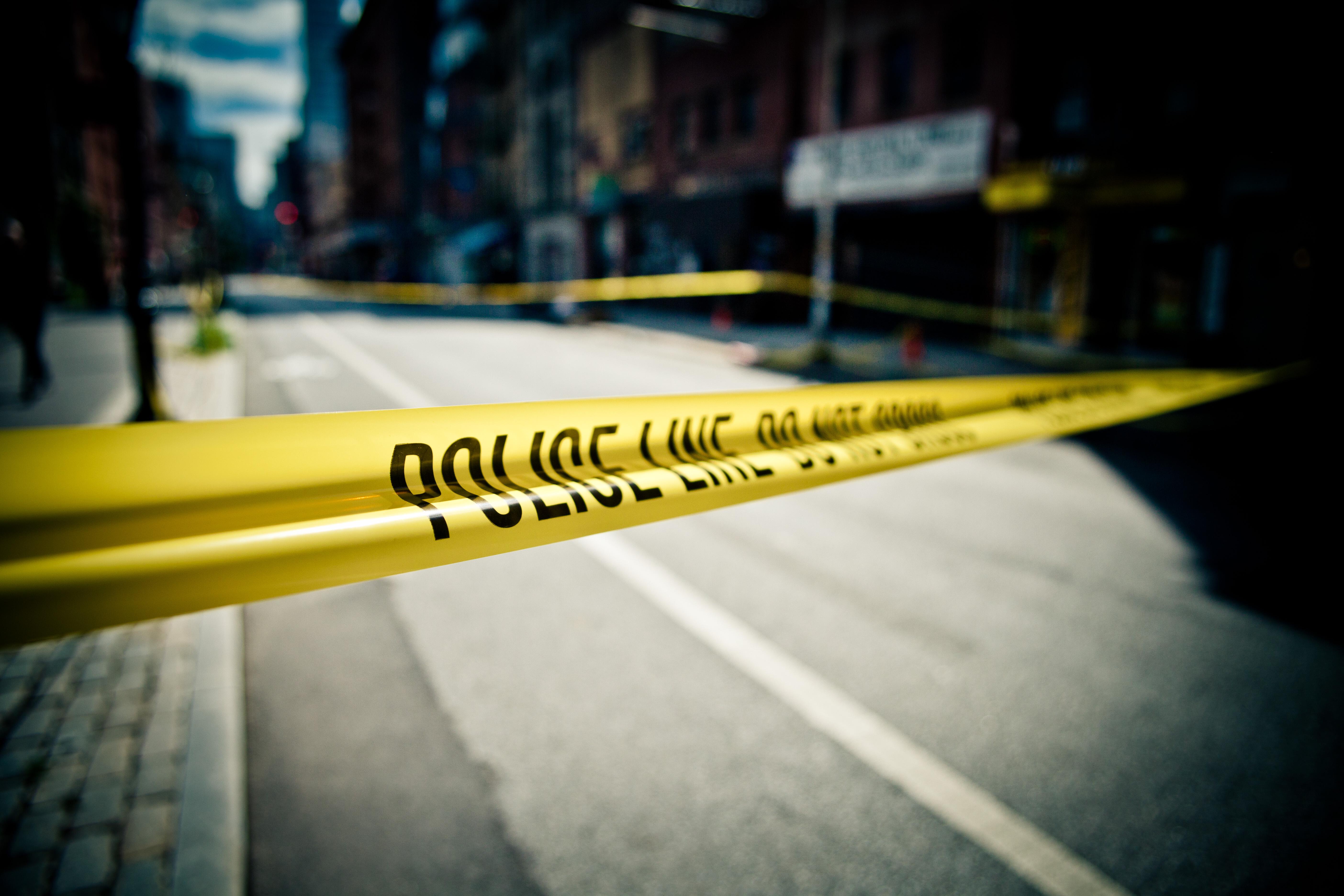 Police tape blocks off a crime scene.