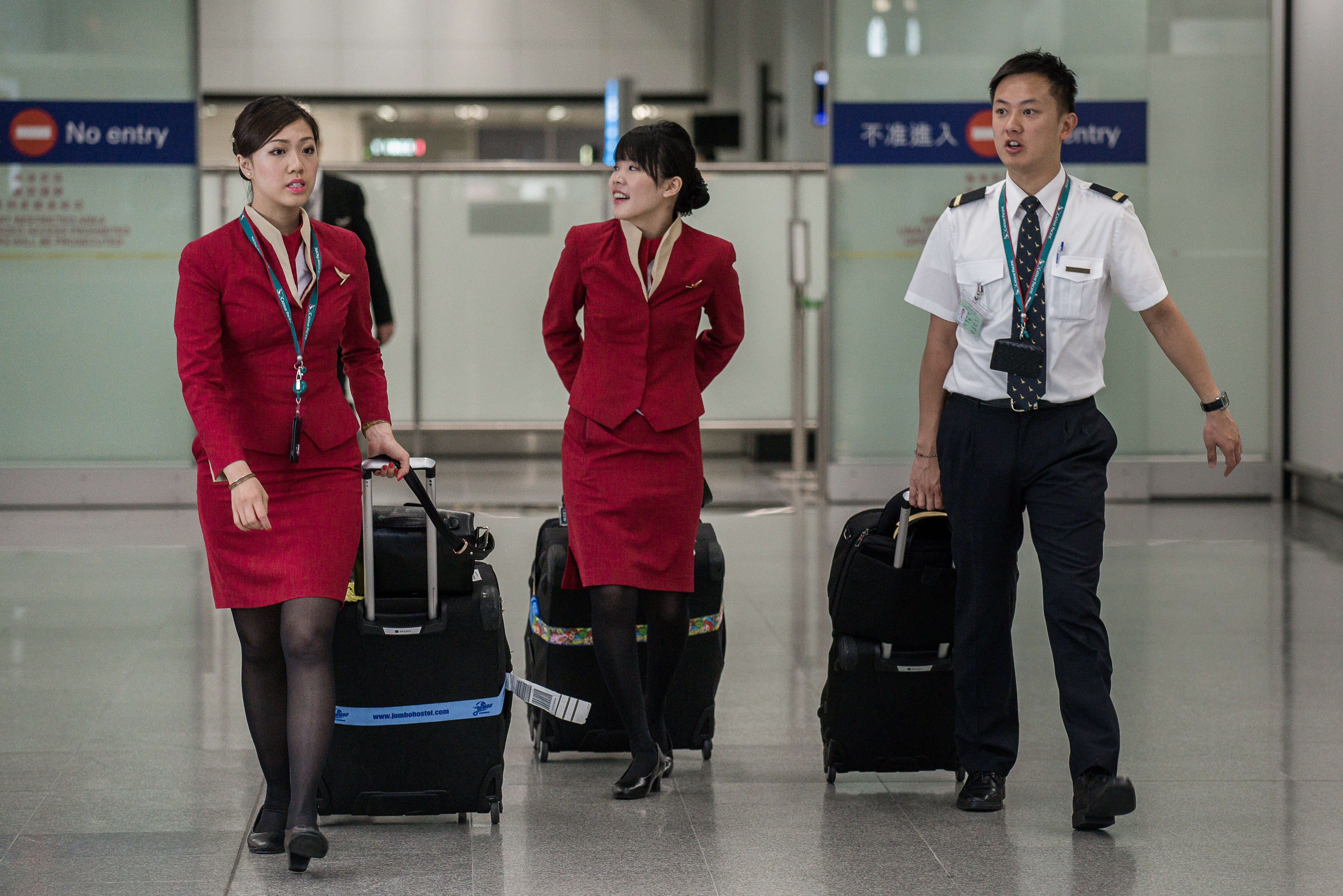 Flight attendants for Cathay Pacific arrive at the international airport in Hong Kong on May 5, 2014.