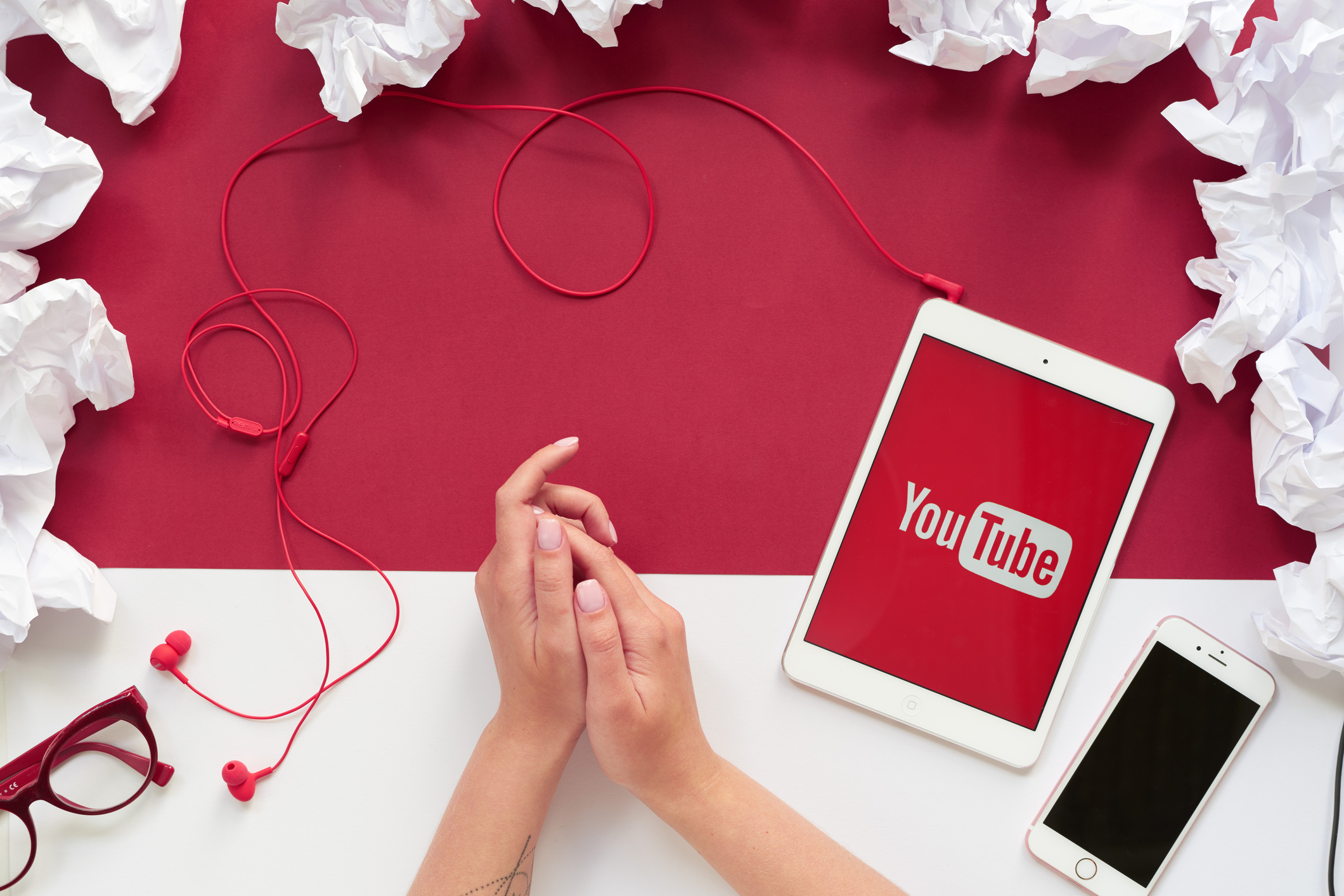 Directly above view of modern devices on table with crumpled papers, youtube sign on tablet screen
