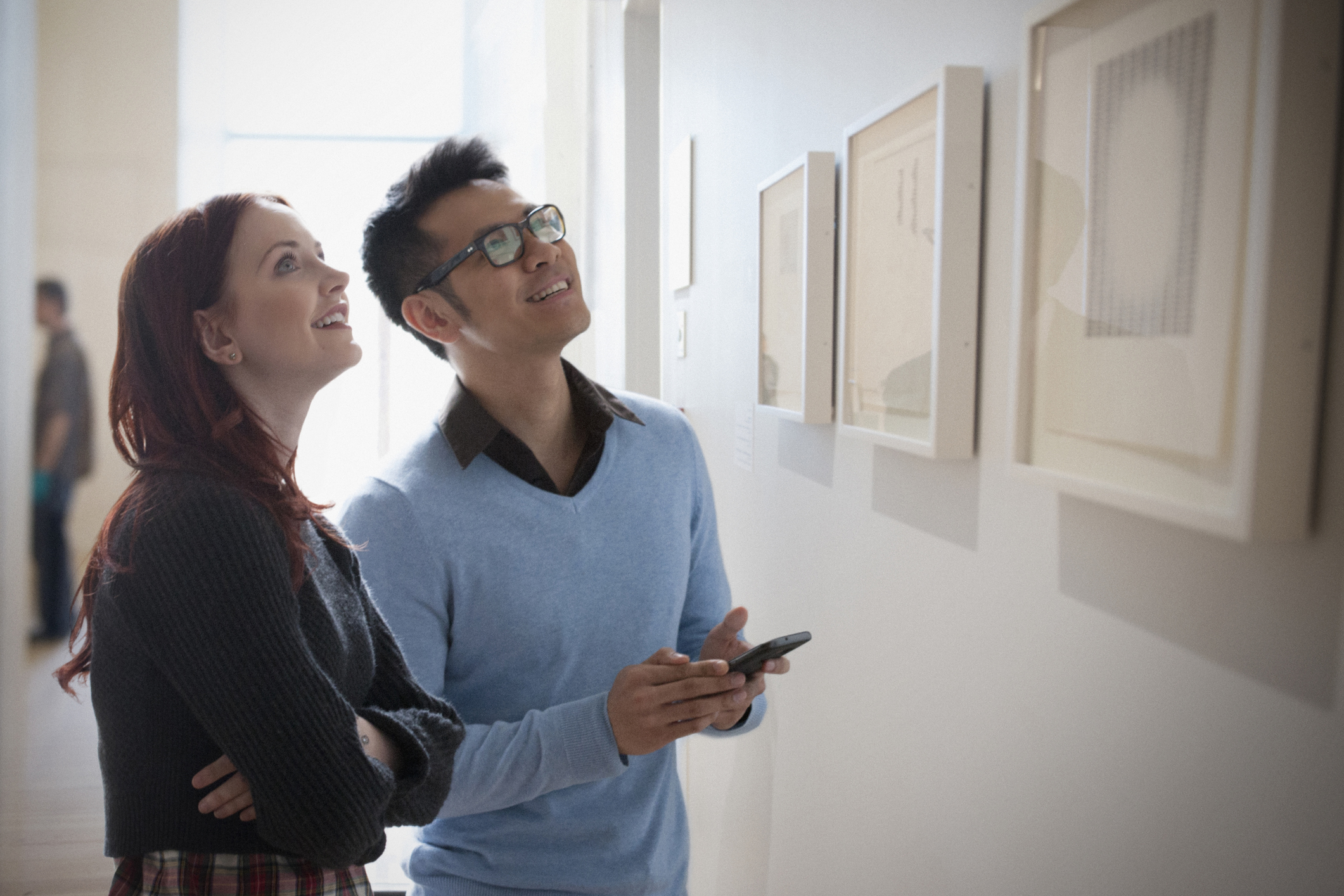 Couple with cell phone admiring artwork in gallery