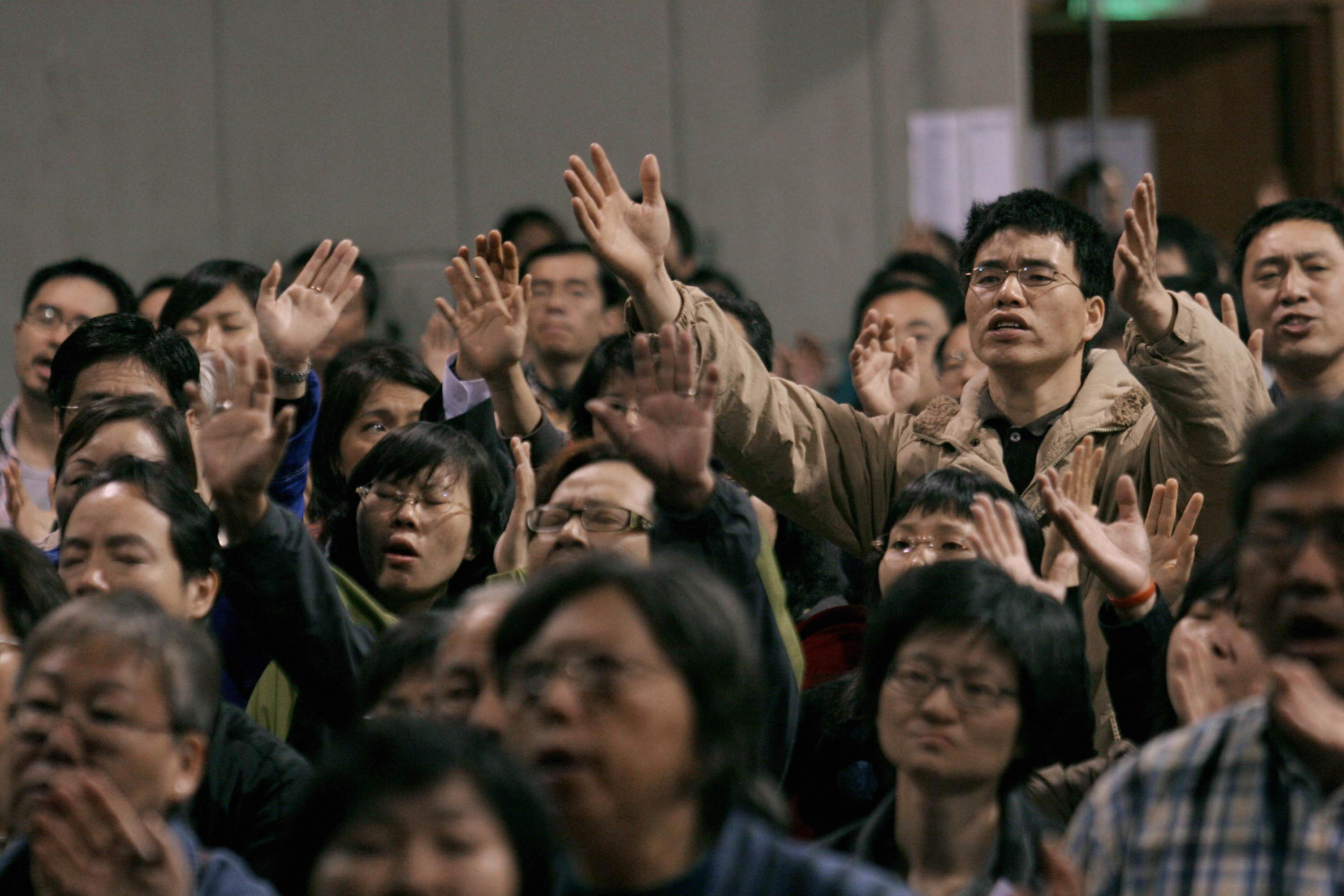 Participants raise their hands in prayer during the first Global Chinese Alpha conference in Hong Kong, April 10, 2007.