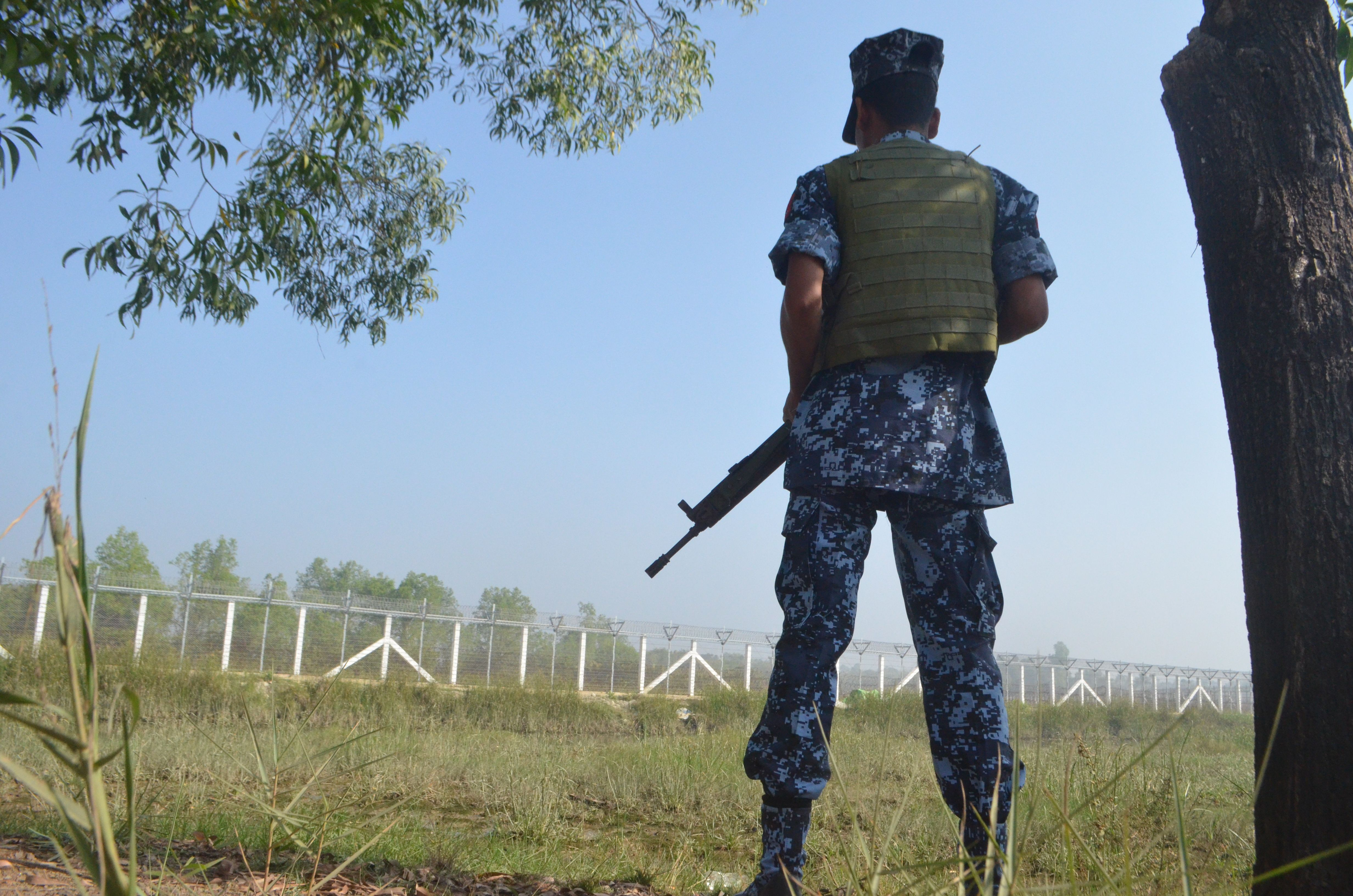 A Myanmar border policeman holds his weapon as he stands near the Taungpyo Bangladesh-Myanmar border gate on the outskirts of Maungdaw in Rakhine state on Jan. 24, 2018.