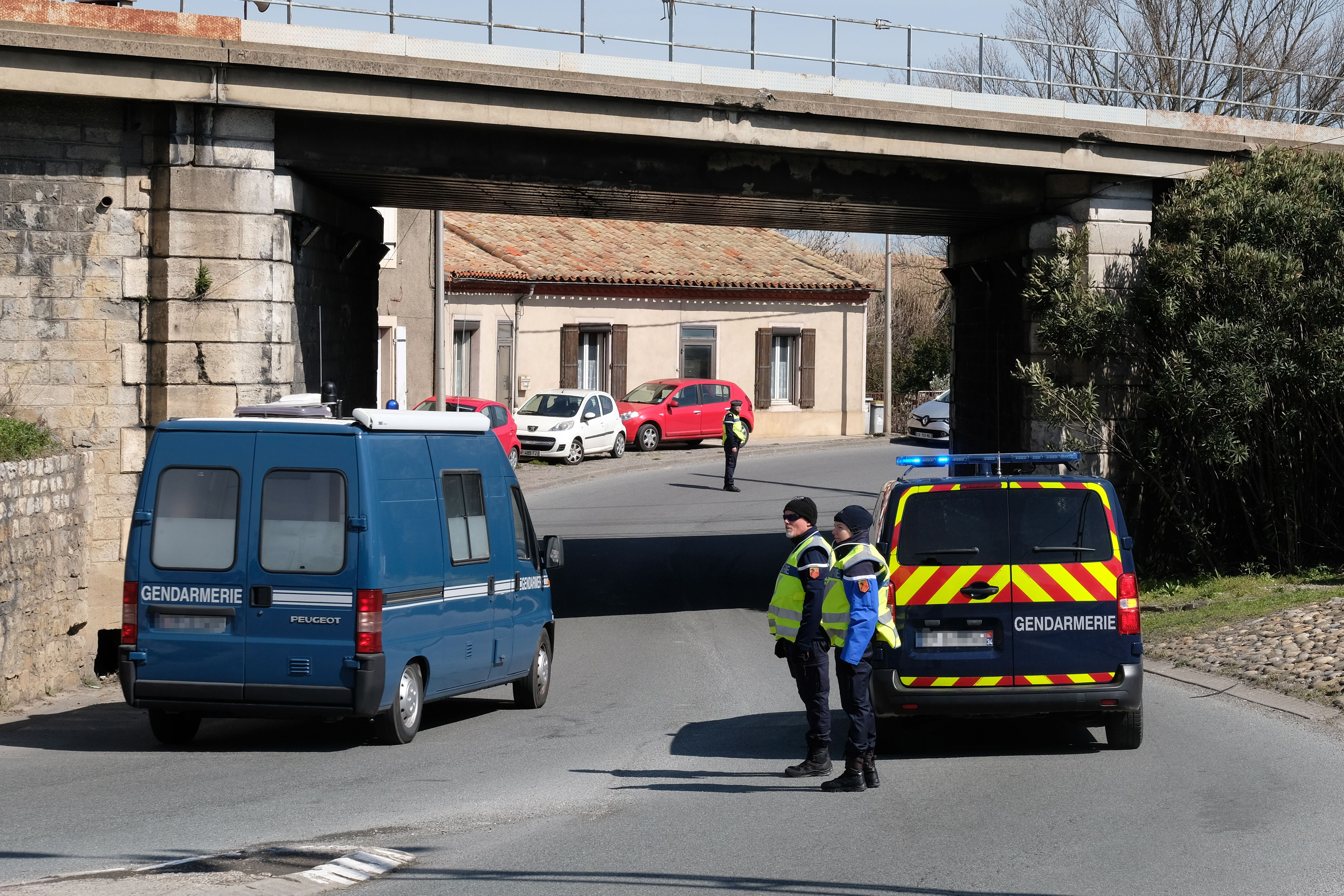 French gendarmes block an access to Trebes, where a man took hostages at a supermarket on March 23, 2018 in Trebes, southwest France. At least two people were killed after a gunman claiming allegiance to the Islamic State group opened fire and took hostages at a supermarket in southwest France. / AFP PHOTO / ERIC CABANIS