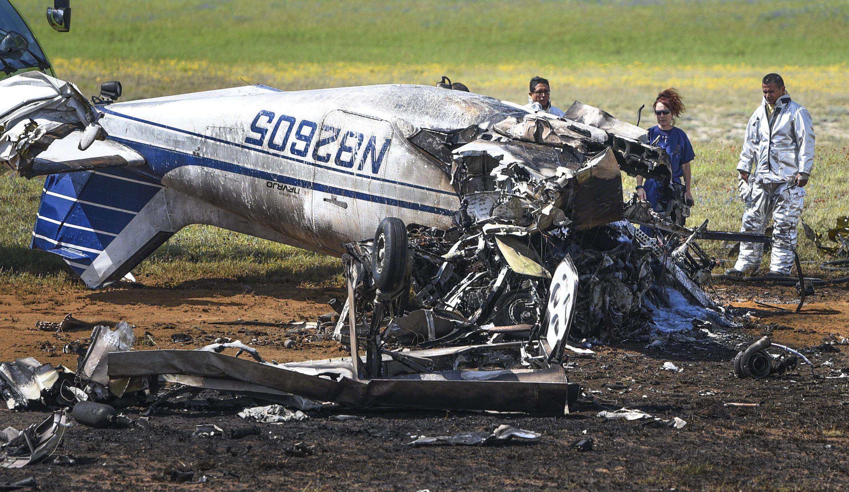 Laredo firefighters and Webb County medical examiner Corinne Stern look through the wreckage of a small plane that crashed at the Laredo International Airport in Laredo, Texas on Mar. 8, 2018.