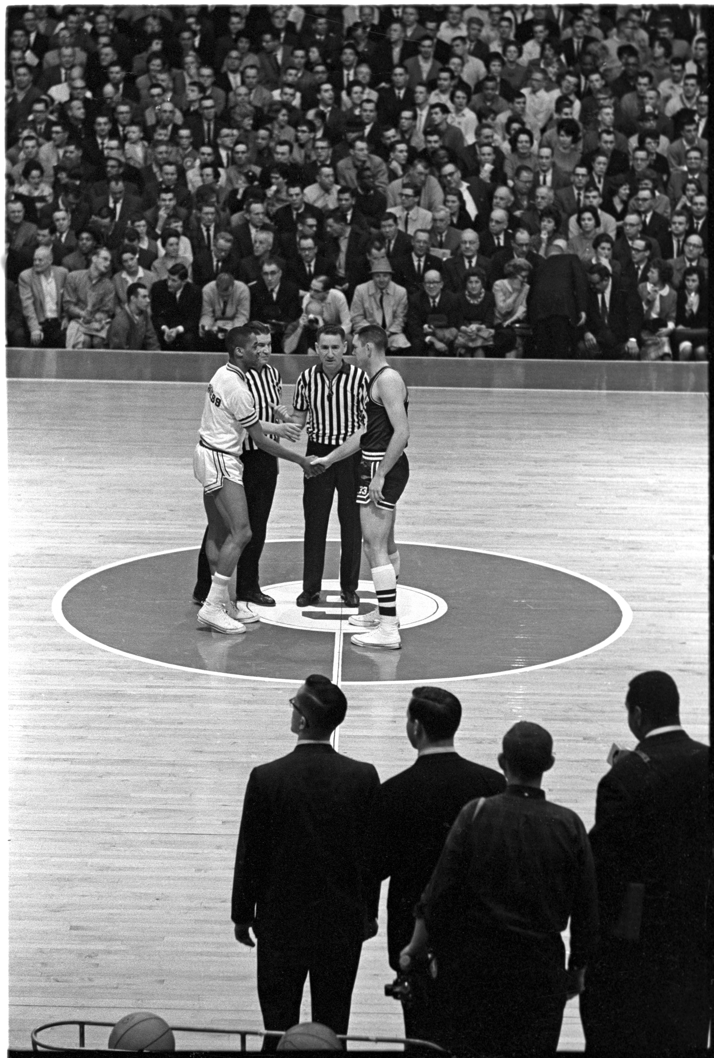 Loyola player Jerry Harkness extends his hand to Joe Dan Gold of Mississippi State on March 15, 1963, before the tip-off of an NCAA tournament game in East Lansing, Michigan.