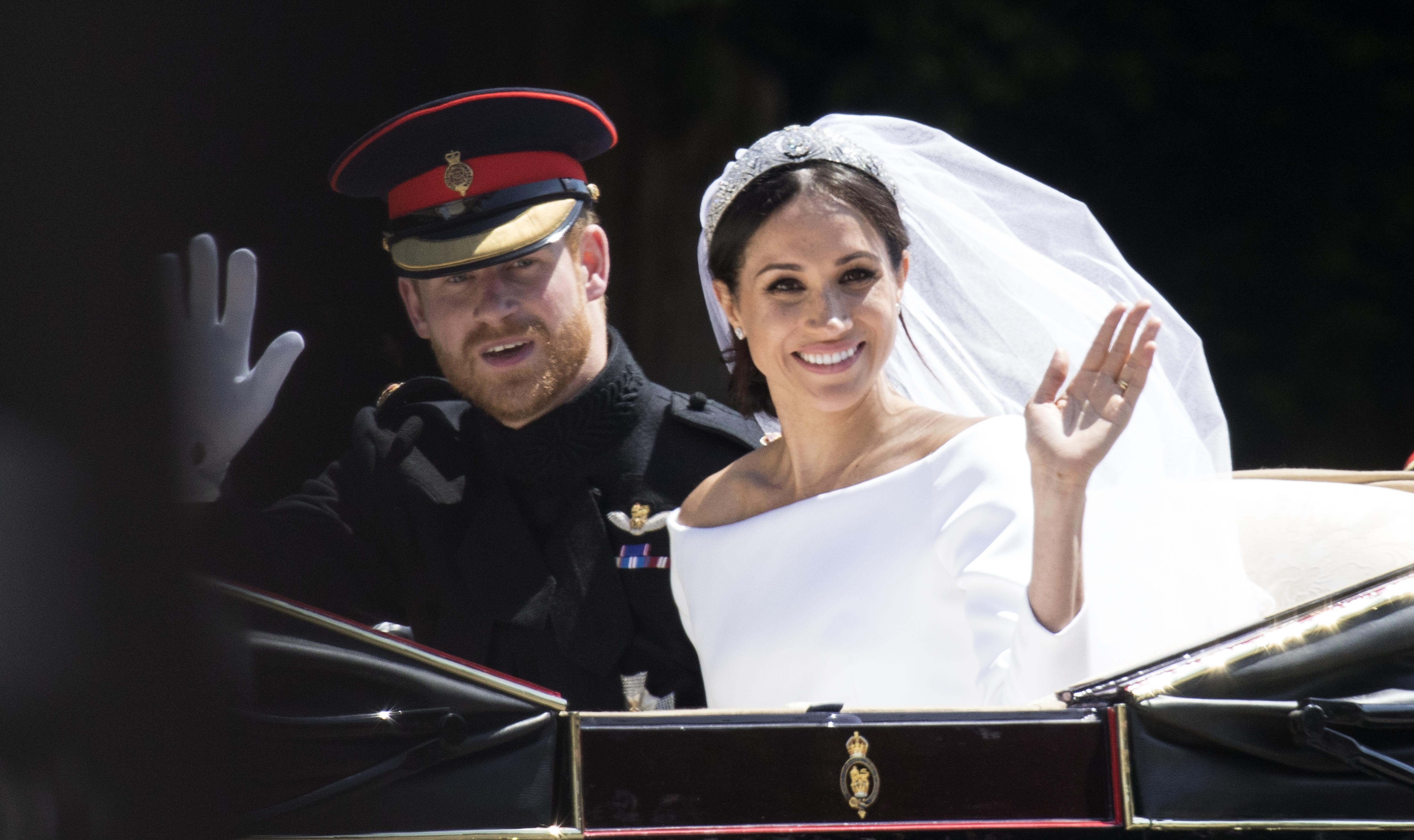 Prince Harry, Duke of Sussex and Meghan, Duchess of Sussex travel in the Ascot Landau Carriage during their carriage procession after their wedding on May 19, 2018 in Windsor, England.