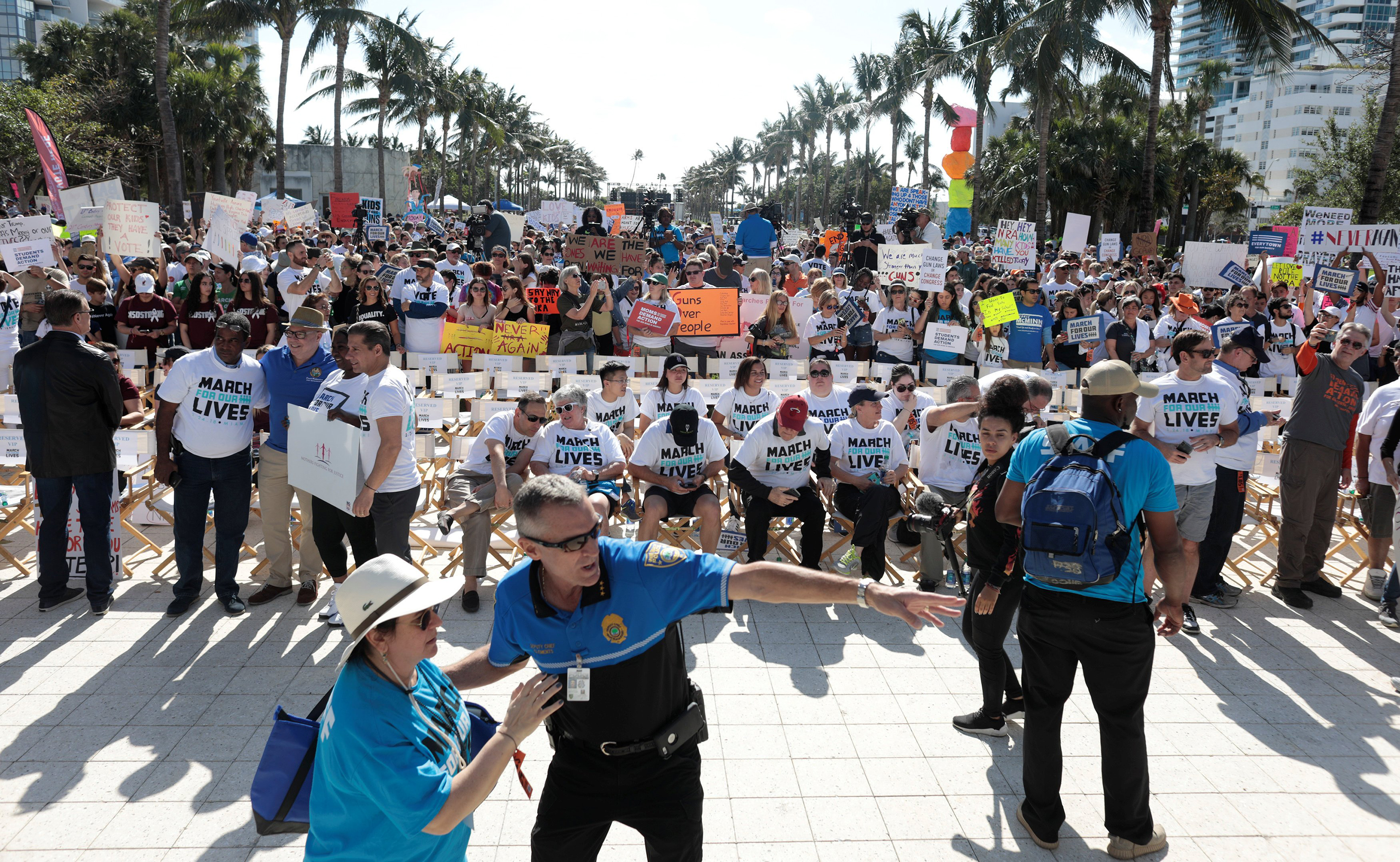 People stand while rallying in the street during the March For Our Lives demonstration, demanding stricter gun control laws, at the Miami Beach Senior High School.