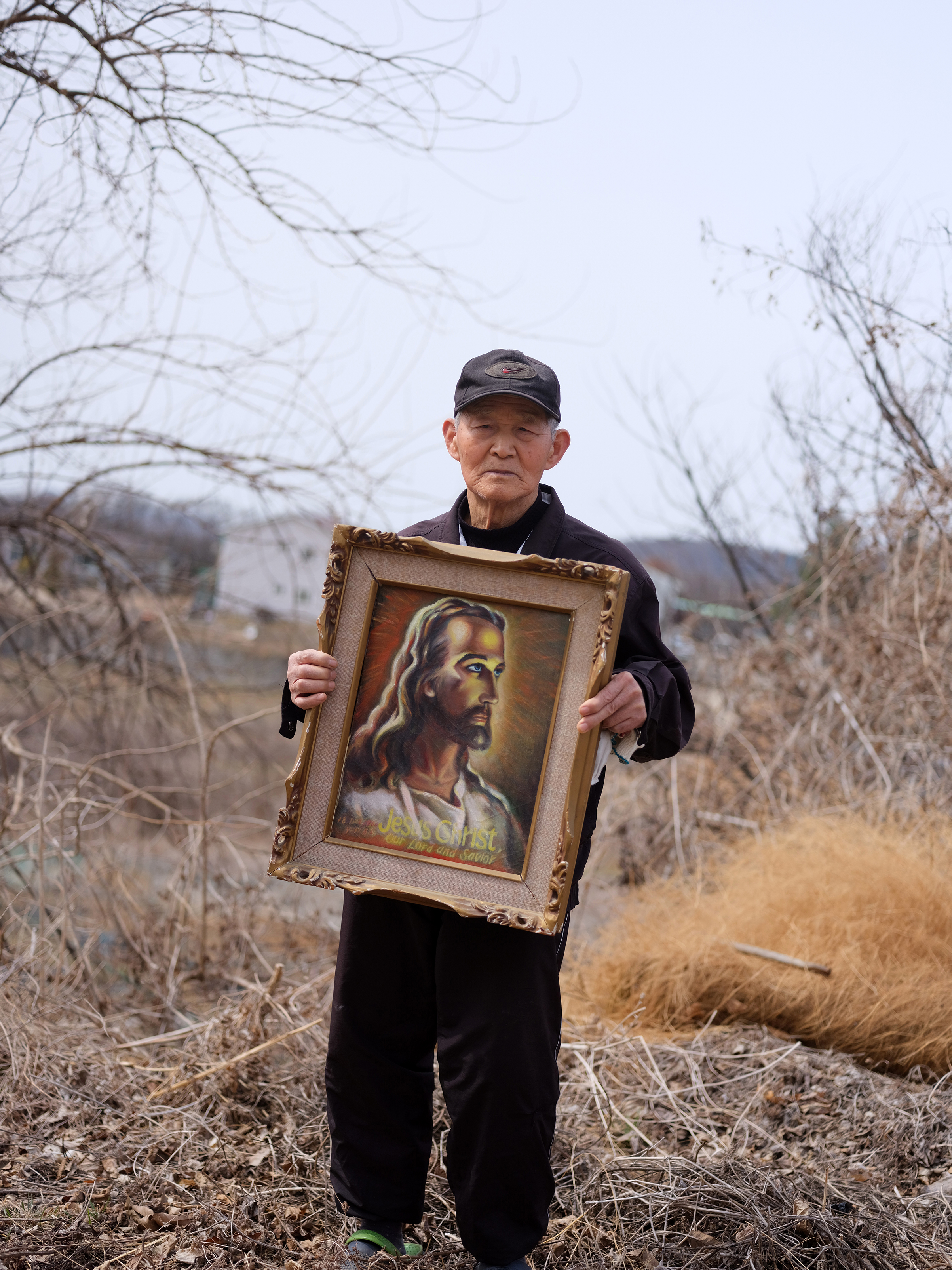 Yoon Seok-sahn, who was separated from his family in the North, poses near his home in Tongilchon.