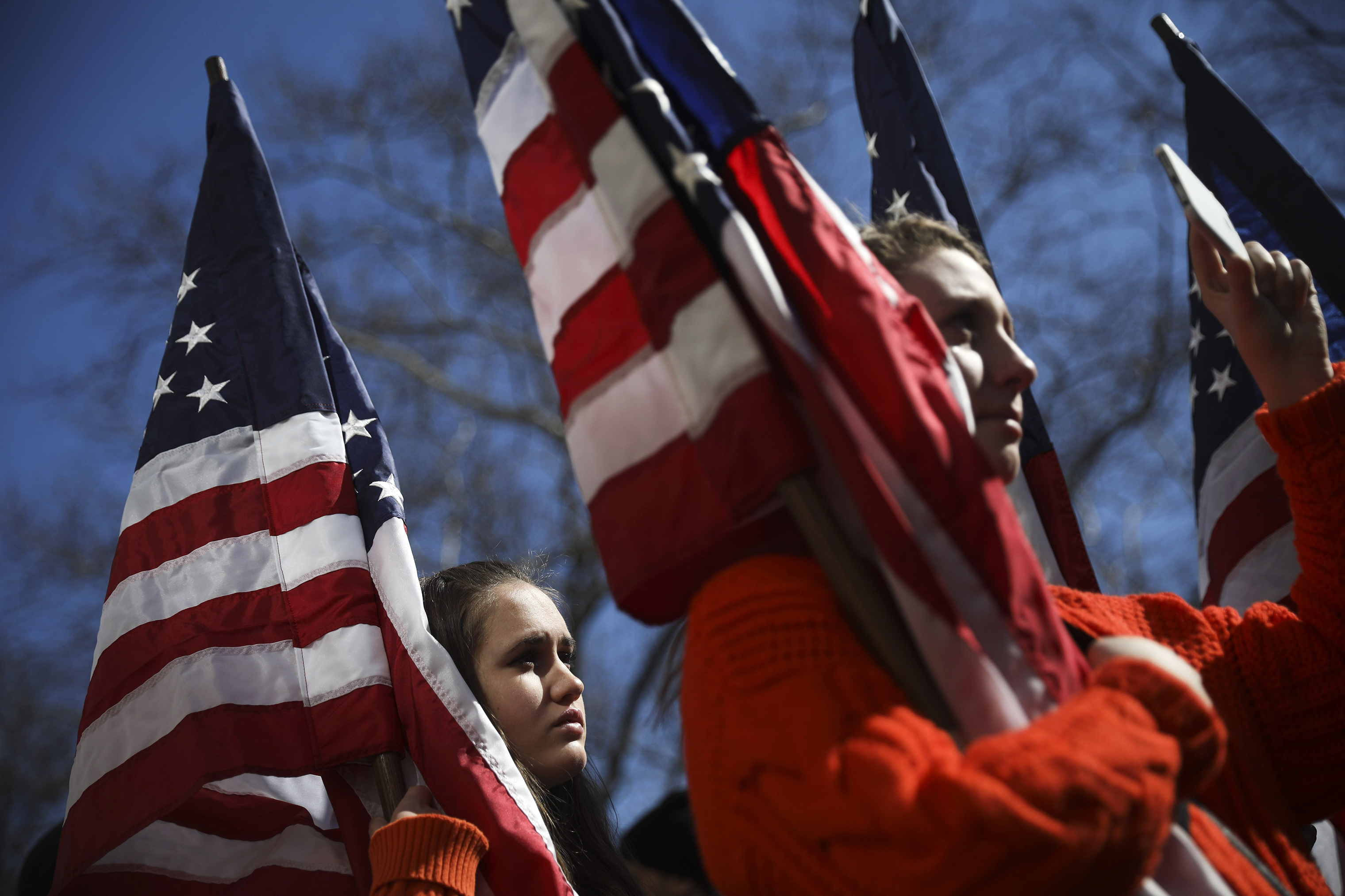 High school students from New Jersey hold American flags as they attend the March For Our Lives near Columbus Circle.