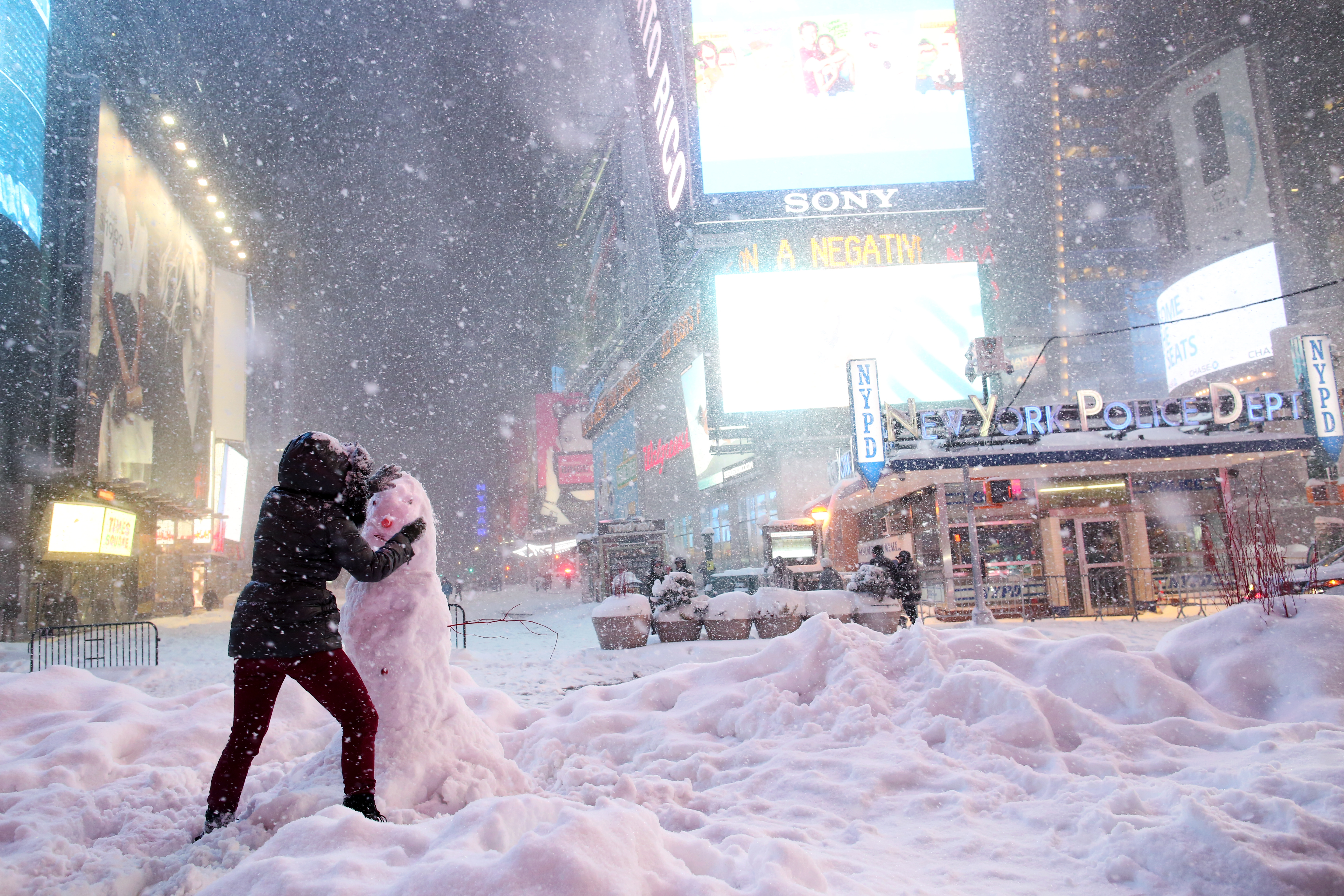 A woman decorates a snowman in Times Square as all cars but emergency vehicles are banned from driving on the road on January 23, 2016 in New York City.