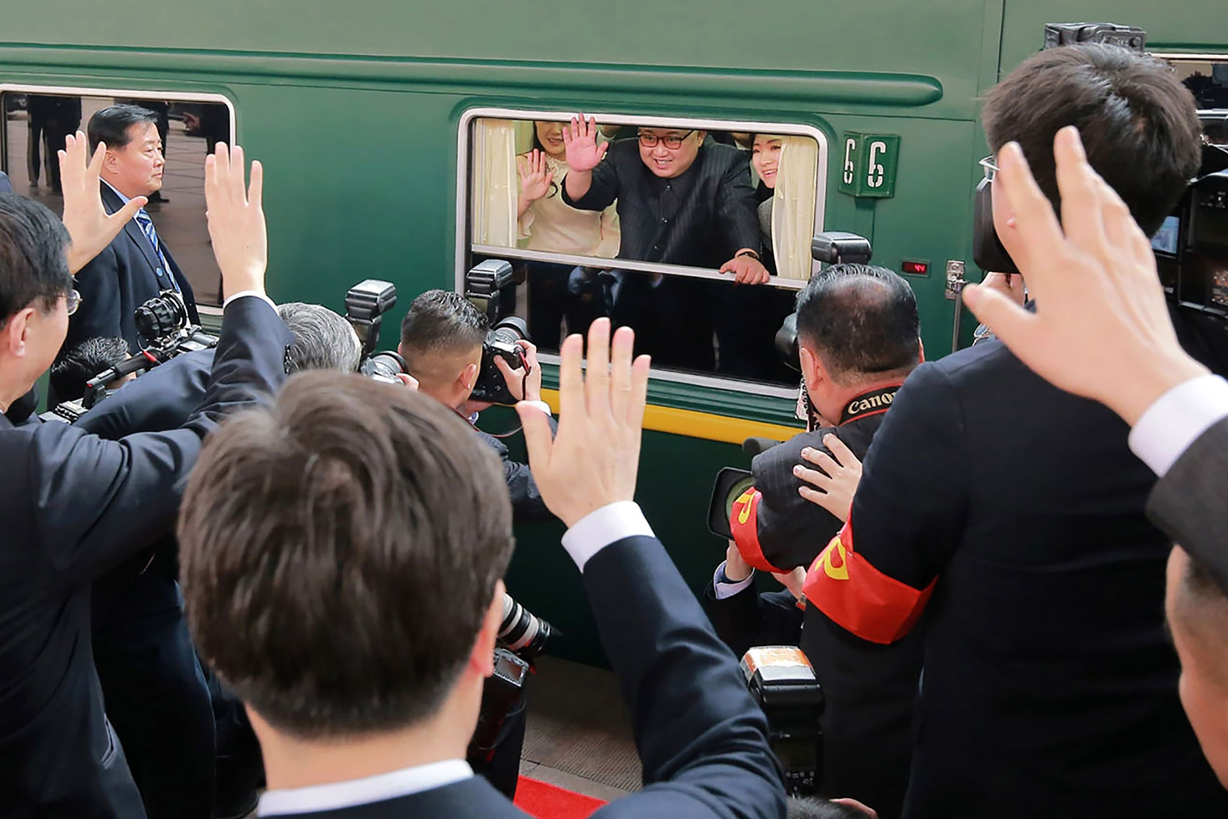 North Korean leader Kim Jong Un waves from his train as it prepares to depart from Beijing railway station