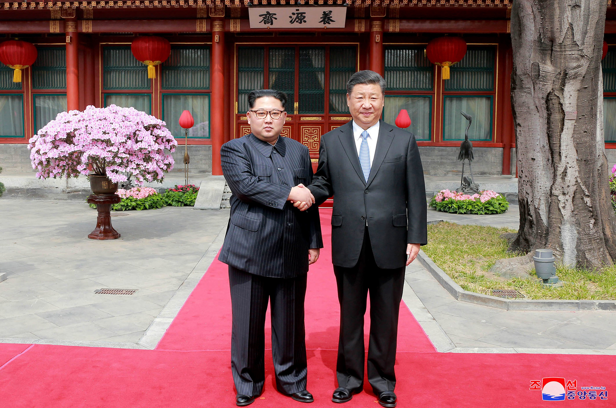 Kim and Xi shake hands at the Diaoyutai State Guesthouse on March 27; Kim waves from his armored train before departing Beijing following his surprise visit