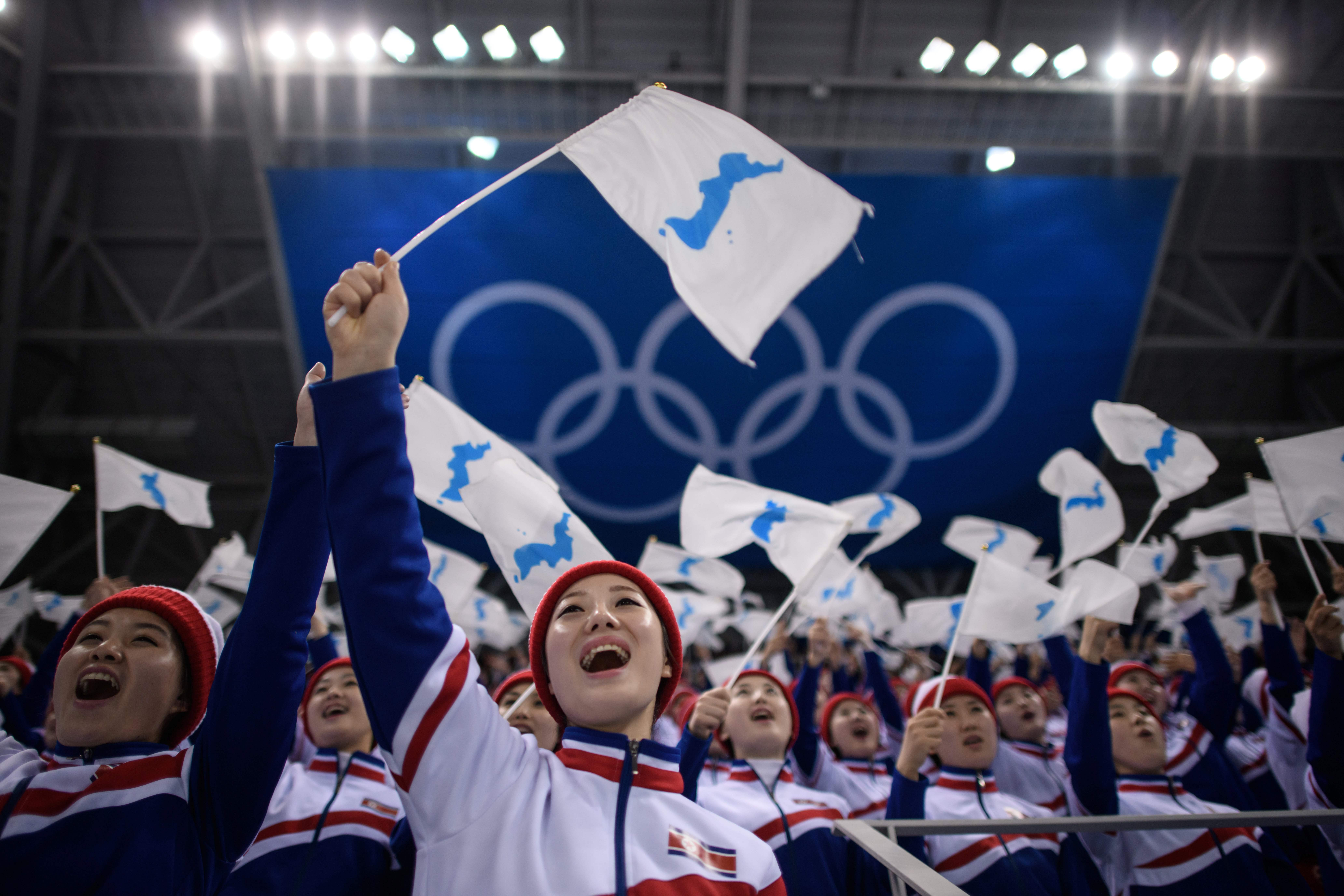 North Korean cheerleaders wave Unified Korea flags during the men's preliminary round ice hockey match between South Korea and Czech Republic during the Pyeongchang 2018 Winter Olympic Games at the Gangneung Hockey Centre in Gangneung on February 15, 2018.