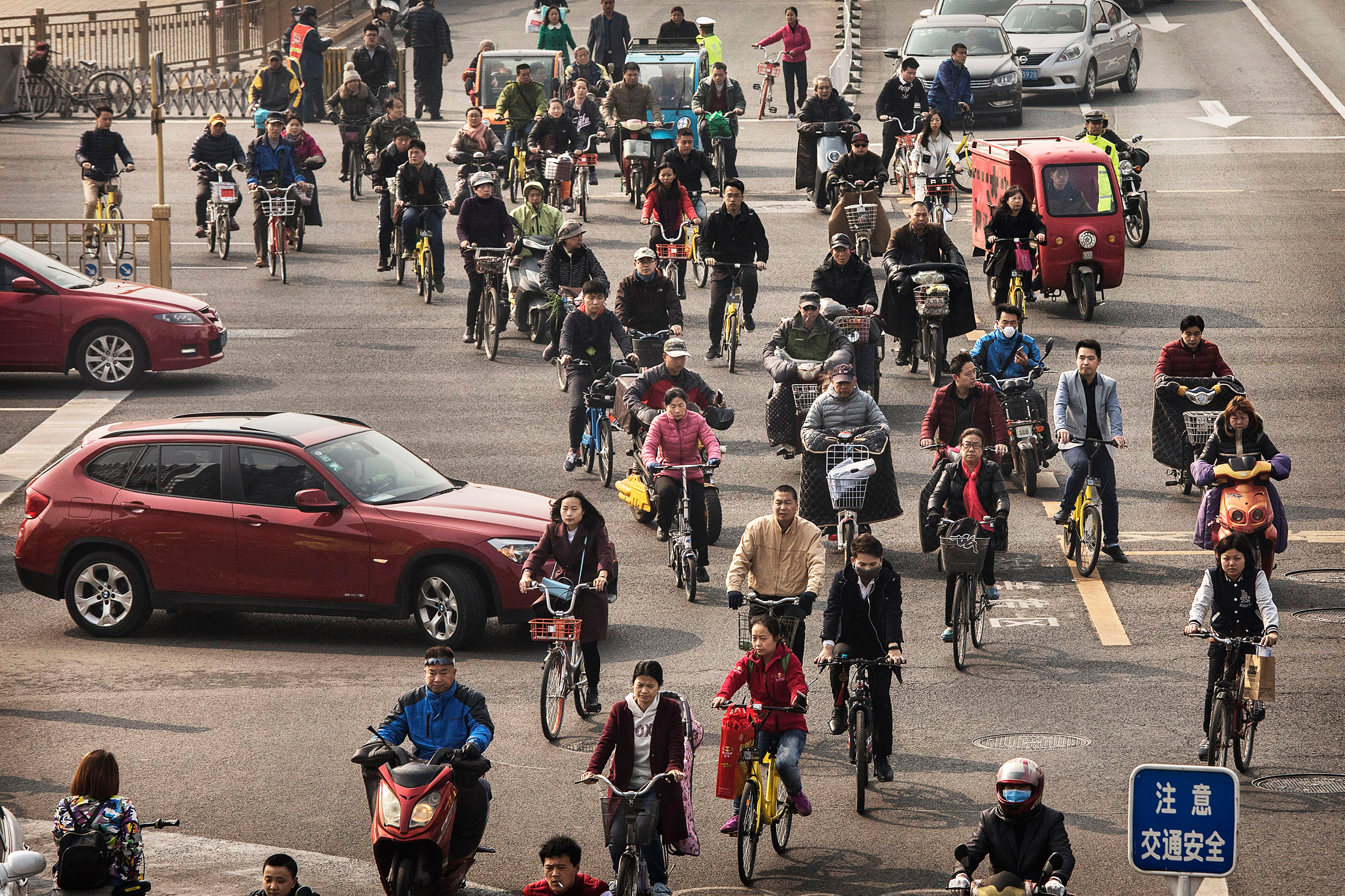 Chinese commuters ride bike shares and other modes of transport in the bicycle lane during rush hour in Beijing on March 29, 2017.