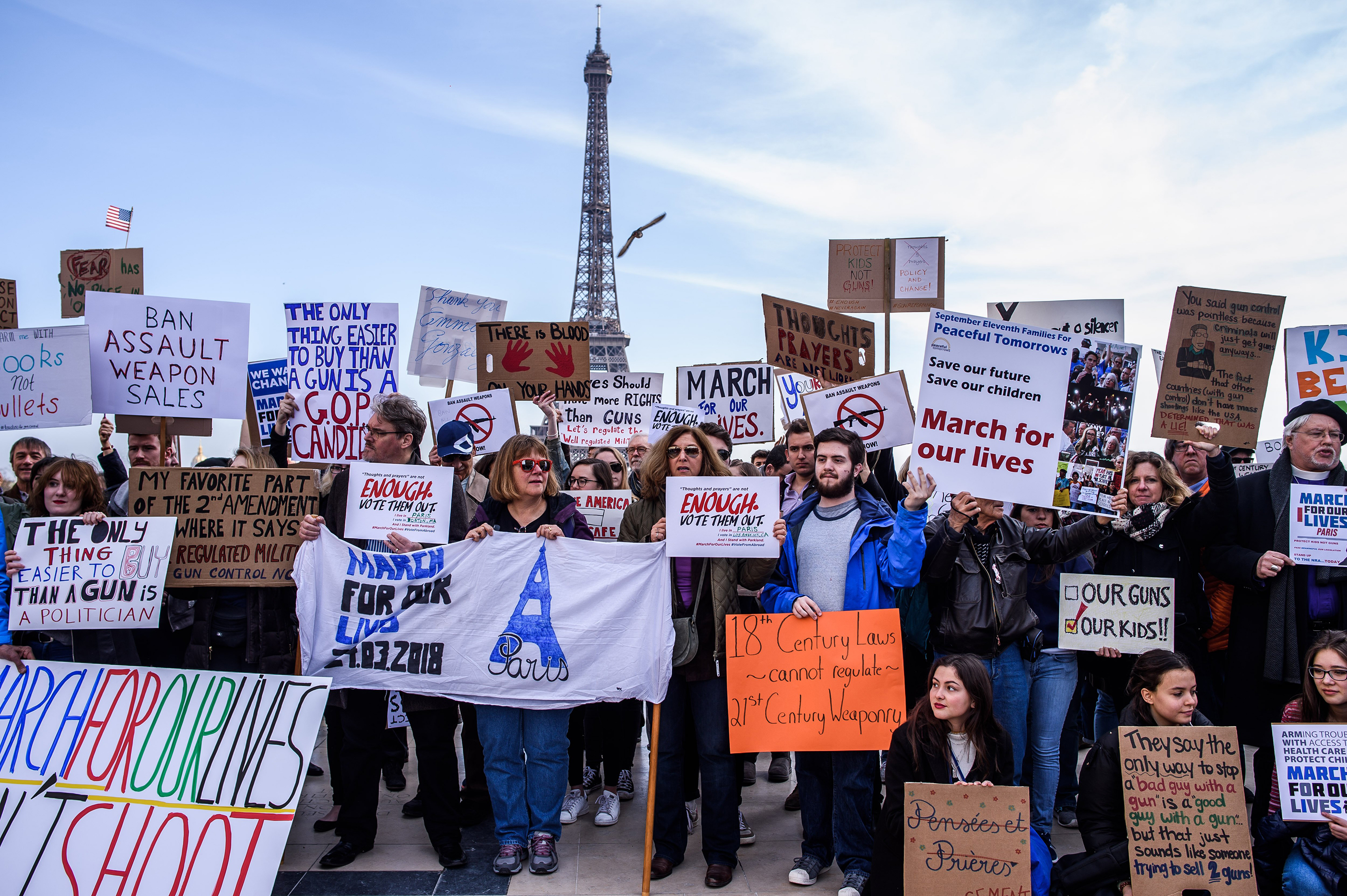 A crowd of French and Americans hold anti-gun posters near the Eiffel Tower.
