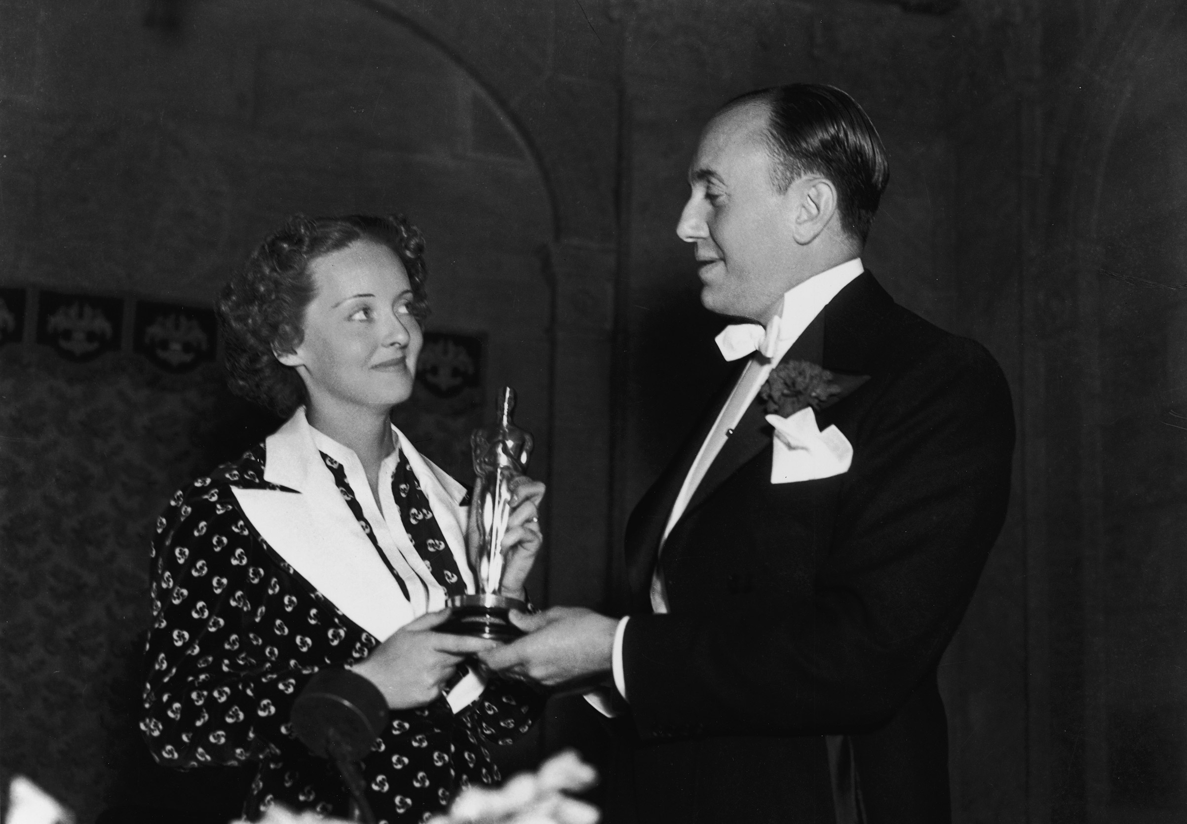 Actor Bette Davis and producer Jack Warner, one of the founders of Warner Bros. Pictures, hold Davis's Oscar for Best Actress for <i>Dangerous</i> at the Biltmore Hotel in Los Angeles, California, on March 5, 1936.