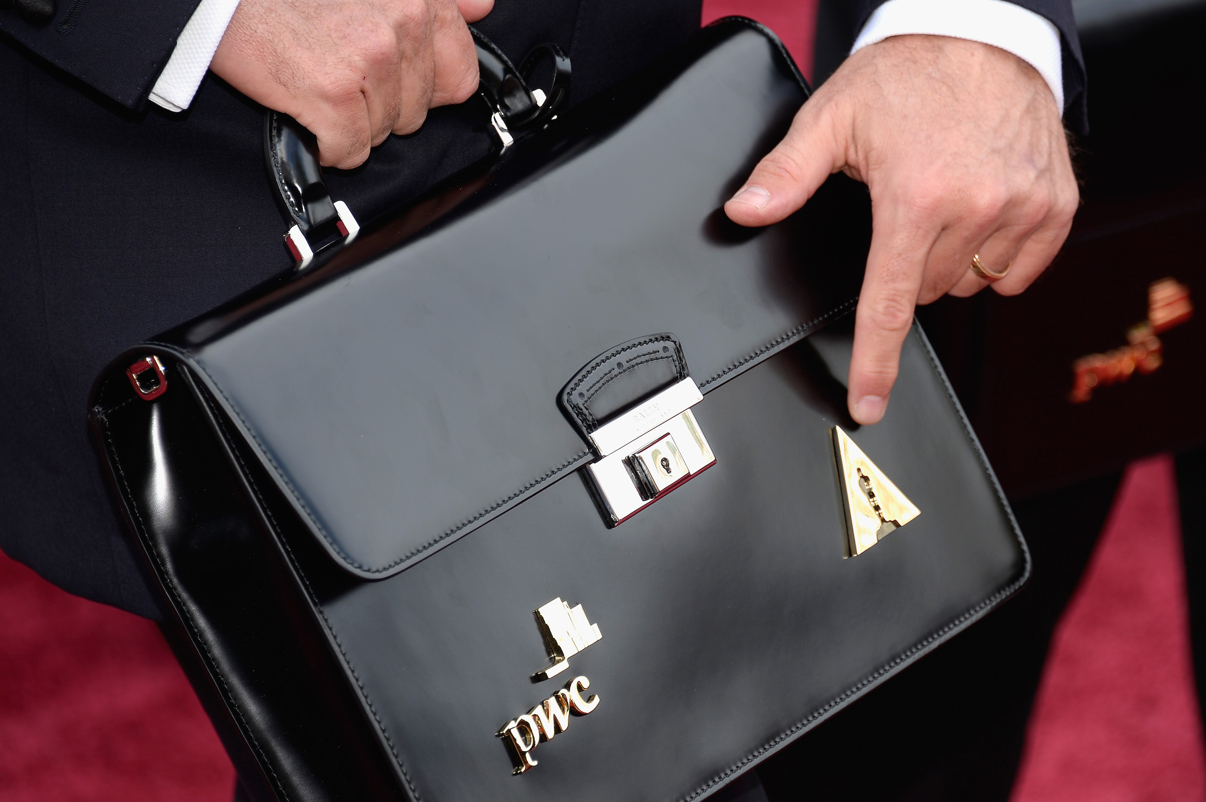 A PricewaterhouseCoopers representative (with a briefcase) attends the Oscars held on March 2, 2014 in Hollywood, Calif.
