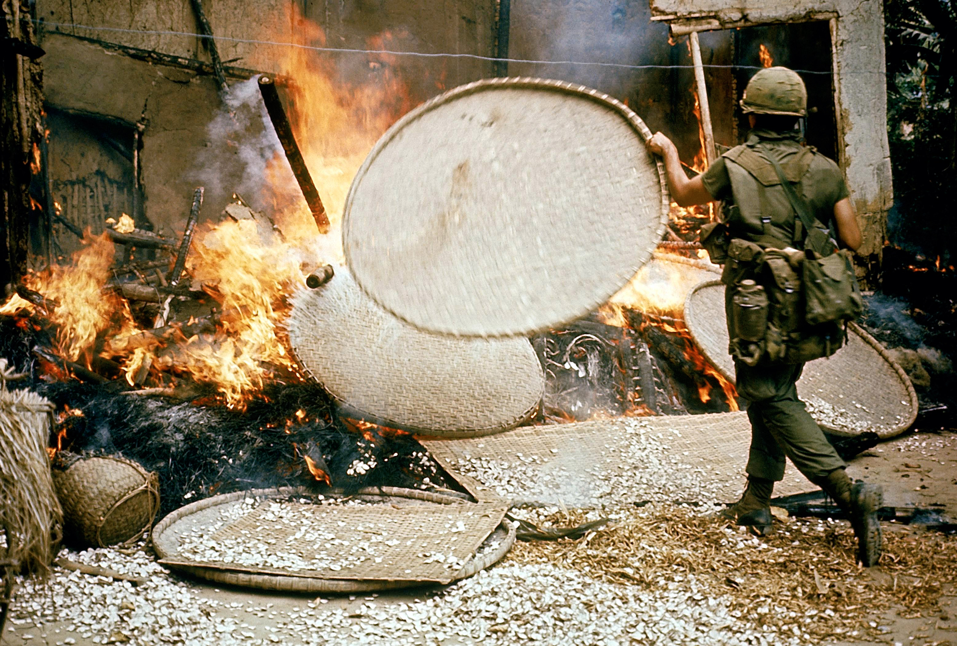 An American soldier stokes the flames of houses that were burned during the massacre in My Lai on March 16, 1968.