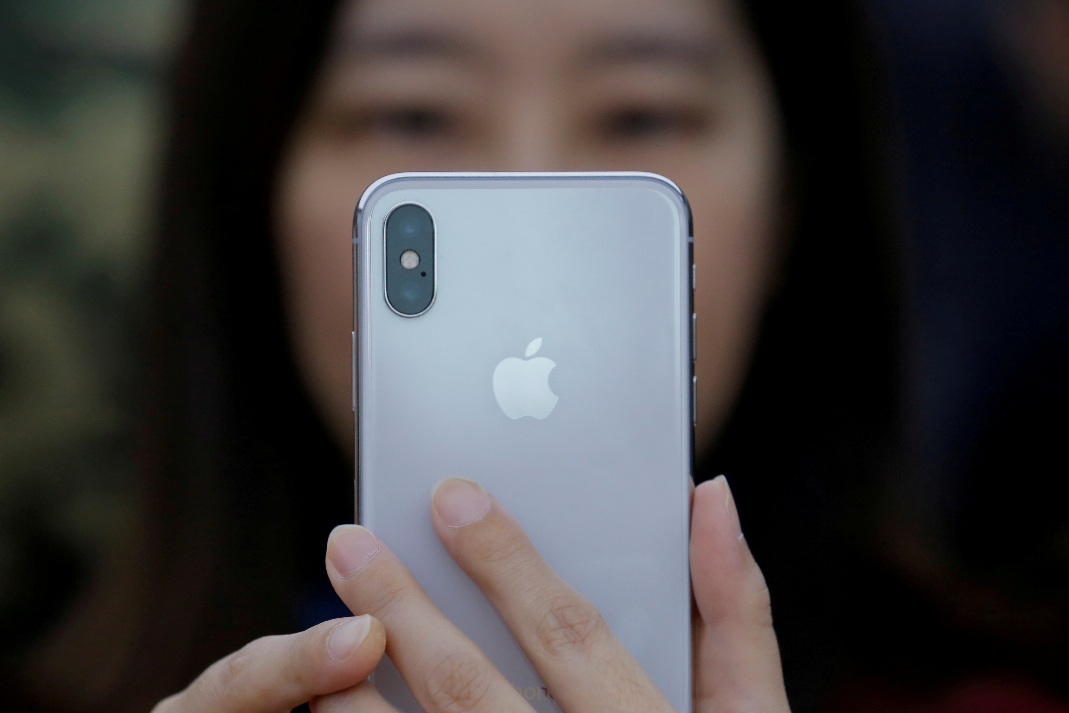 A woman uses an iPhone X during a presentation in Beijing, China on Oct. 31, 2017.