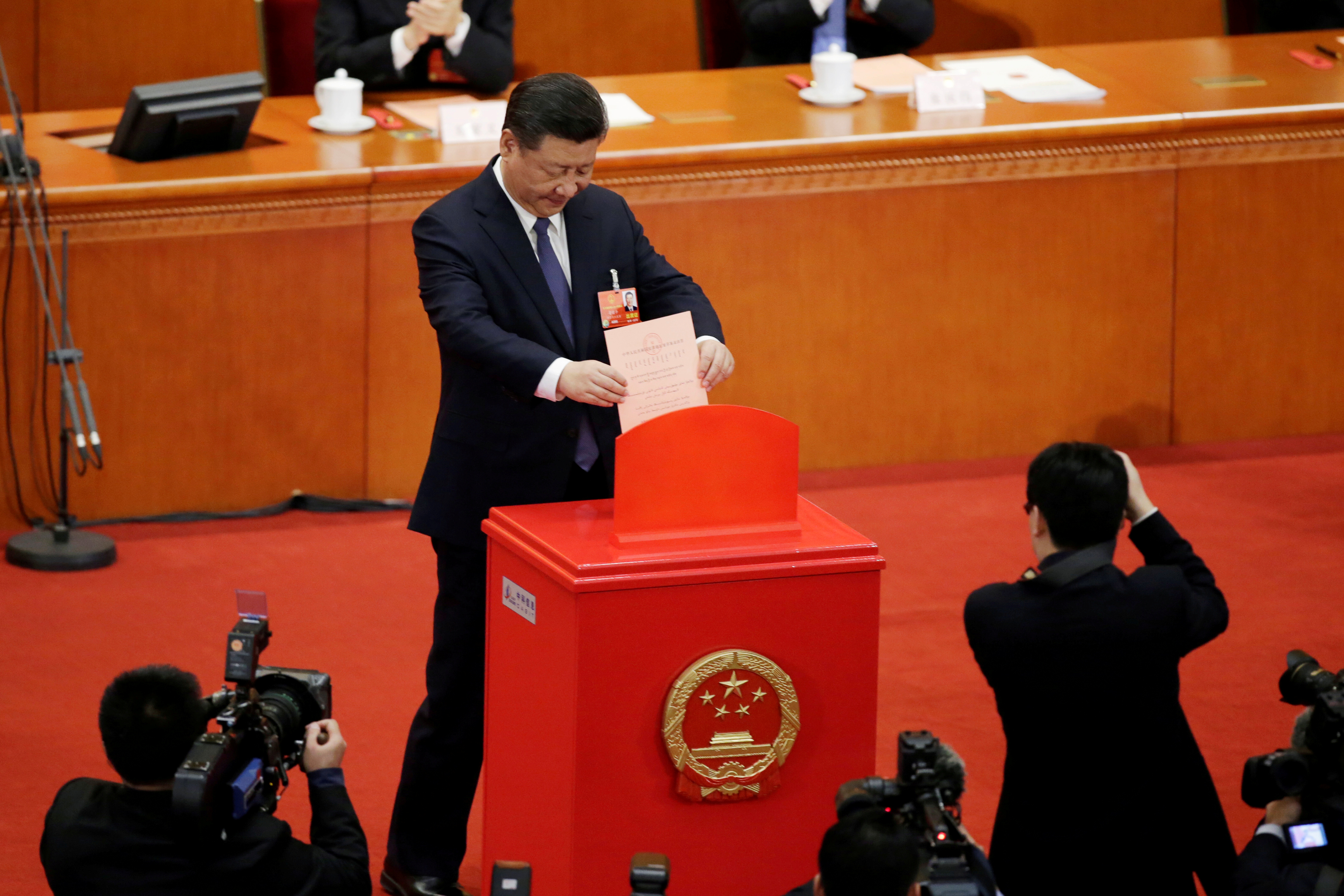 Chinese President Xi Jinping drops his ballot, during a vote on a constitutional amendment lifting presidential term limits, at the National People's Congress (NPC) at the Great Hall of the People in Beijing, China March 11, 2018.
