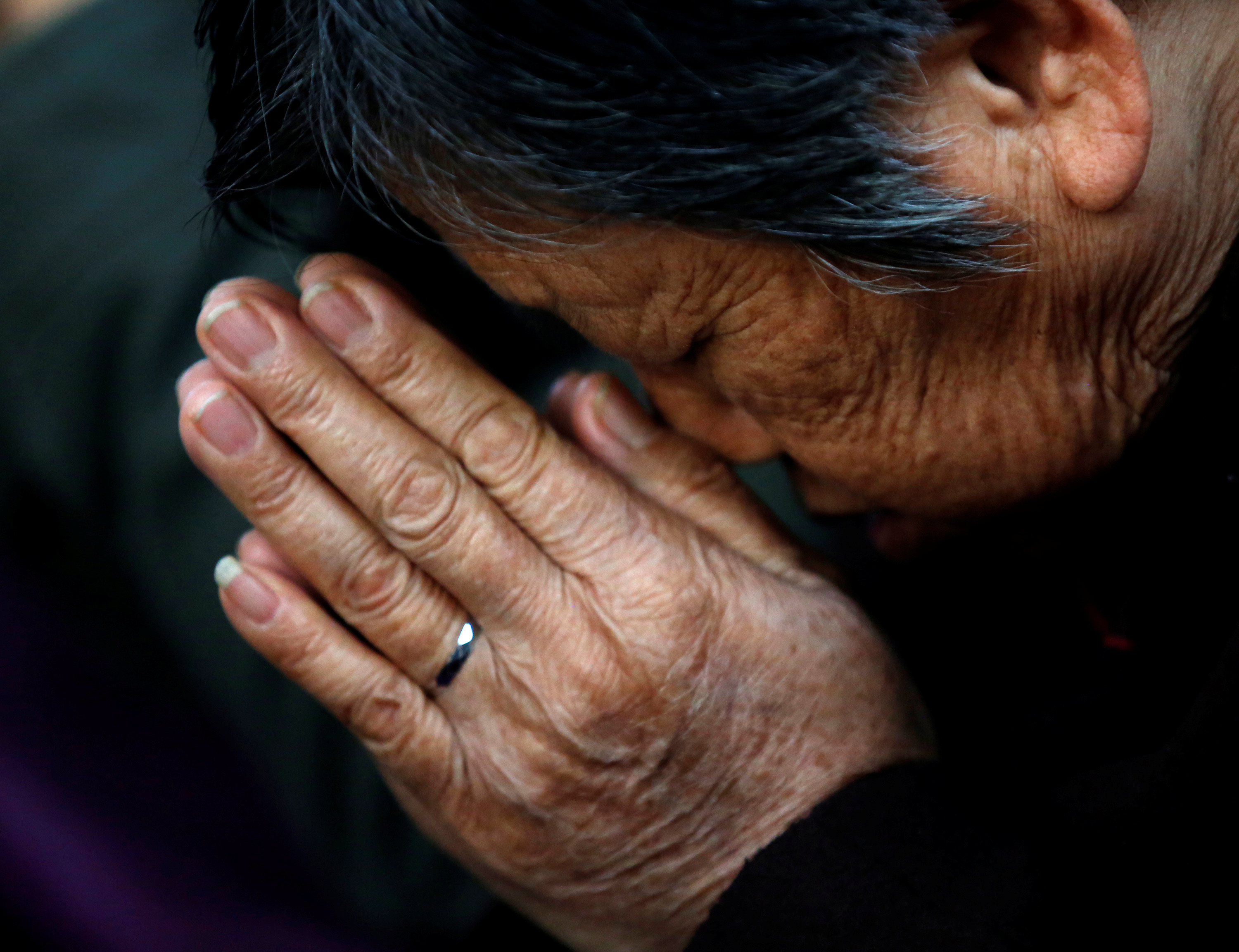 A believer prays during a weekend mass at an underground Catholic church in Tianjin in Nov. 10, 2013.