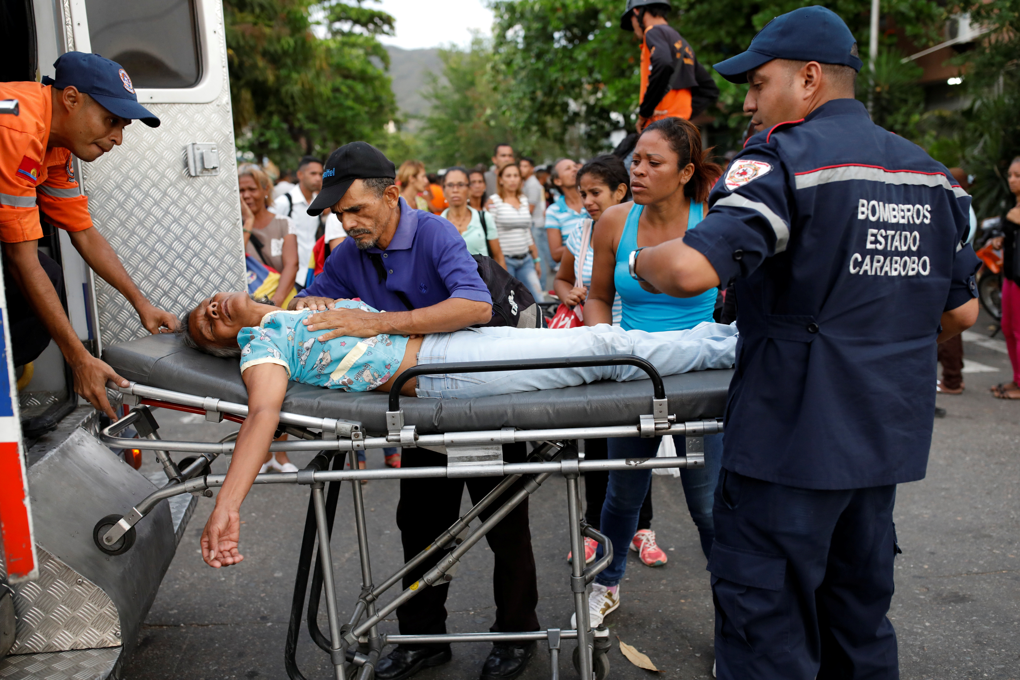 Paramedics help a woman who fainted outside the lockup where a fire occurred in Valencia, Venezuela on March 28, 2018.