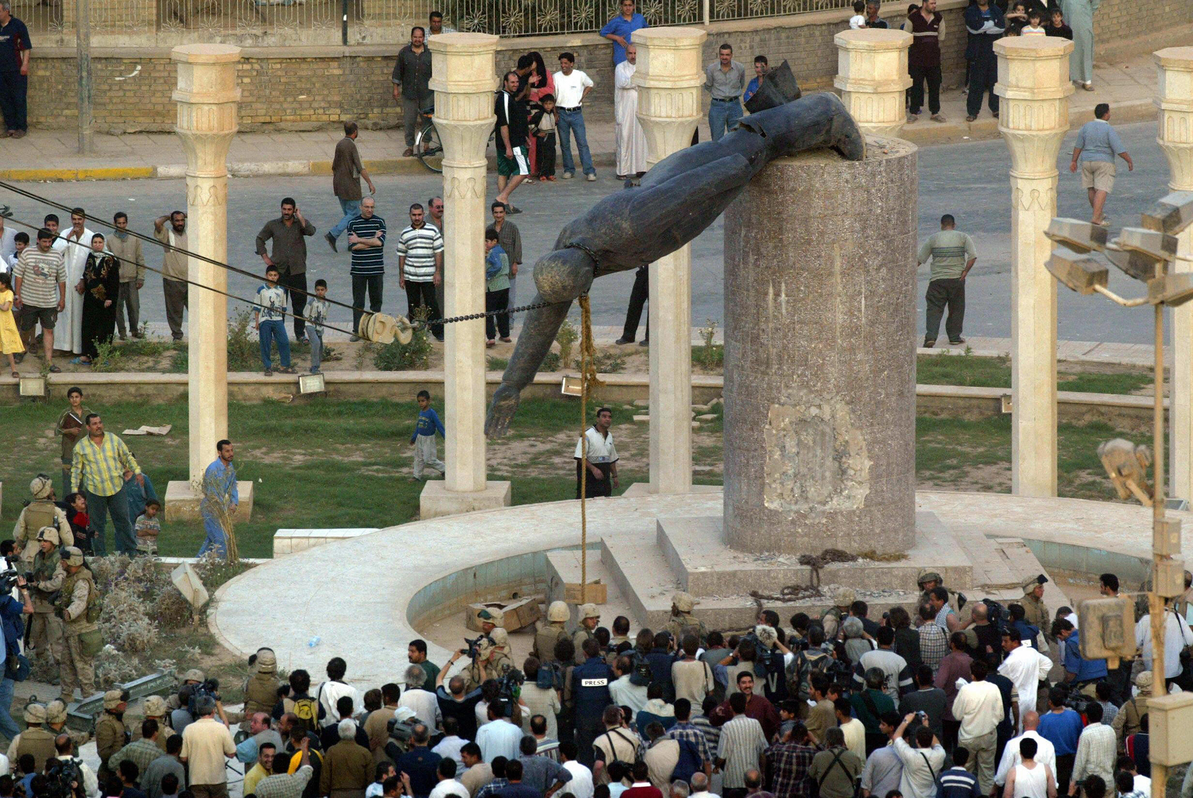 Iraqis watch a statue of Saddam Hussein falling in Baghdad on April 9, 20013. The ousted dictator was hanged in December 2006.