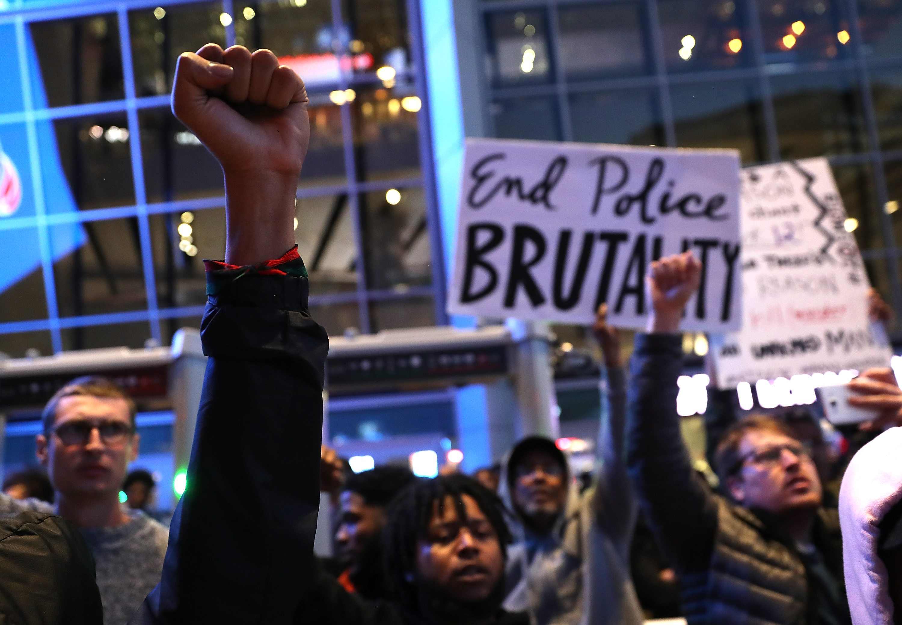 Black Live Matter protesters hold their fists in the air as they block the entrance to the Golden 1 Center during a demonstration on March 22, 2018 in Sacramento.