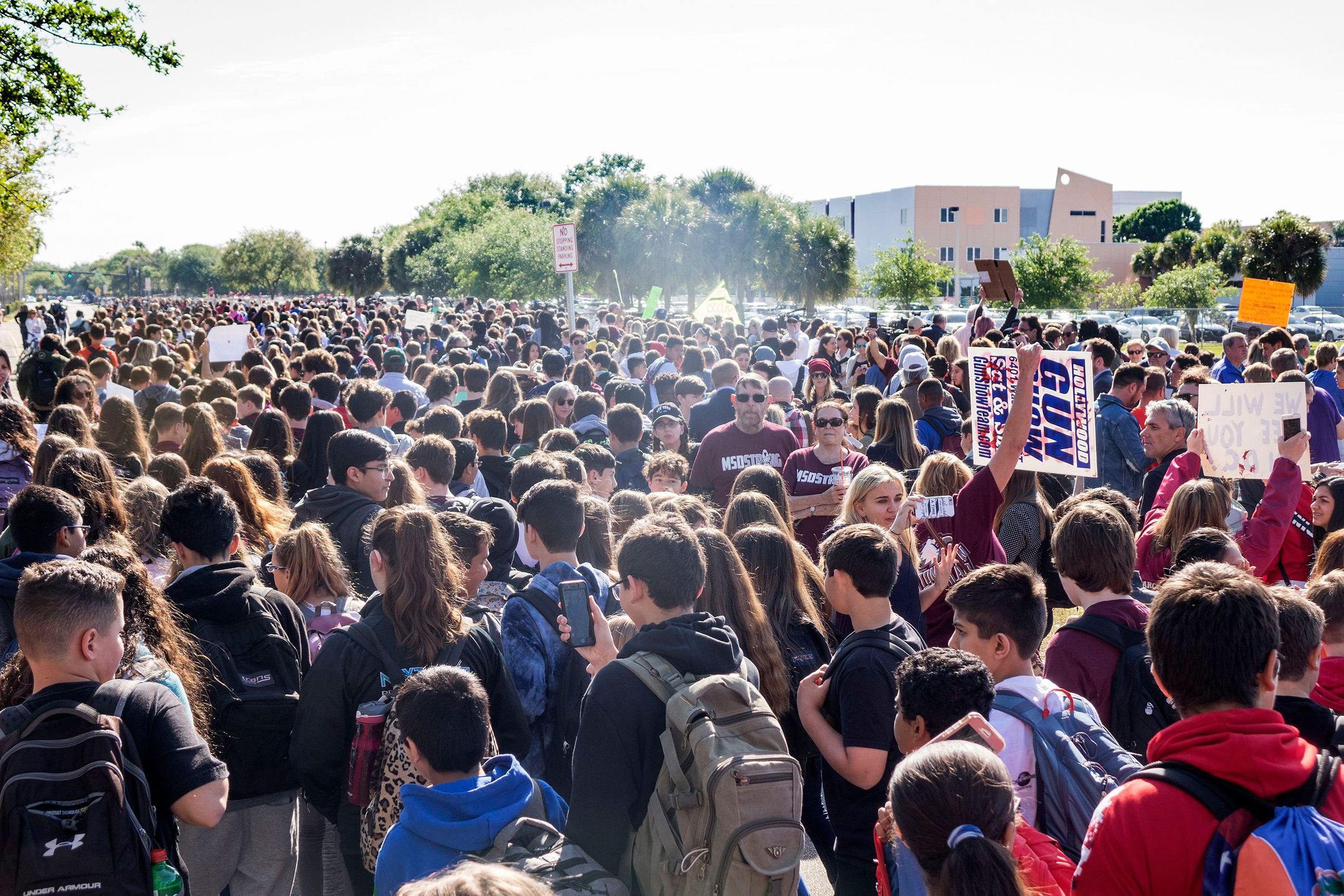Community members and students participate in the national school walkout outside the Marjory Stoneman Douglas High School in Parkland, Fla., on March 14, 2018.
