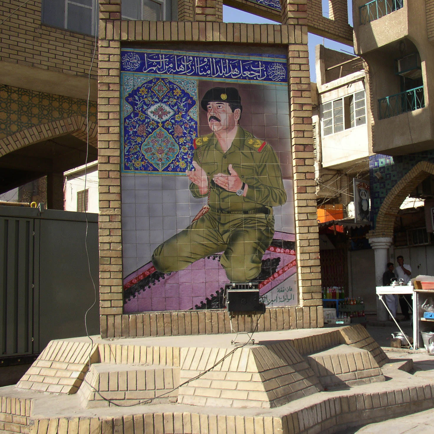 A now-destroyed tile mural showing Saddam Hussein, a Sunni who treated Shi'ites brutally and was despised by Karbala's residents, praying in a military uniform, in the holy Shi'ite city of Karbala.