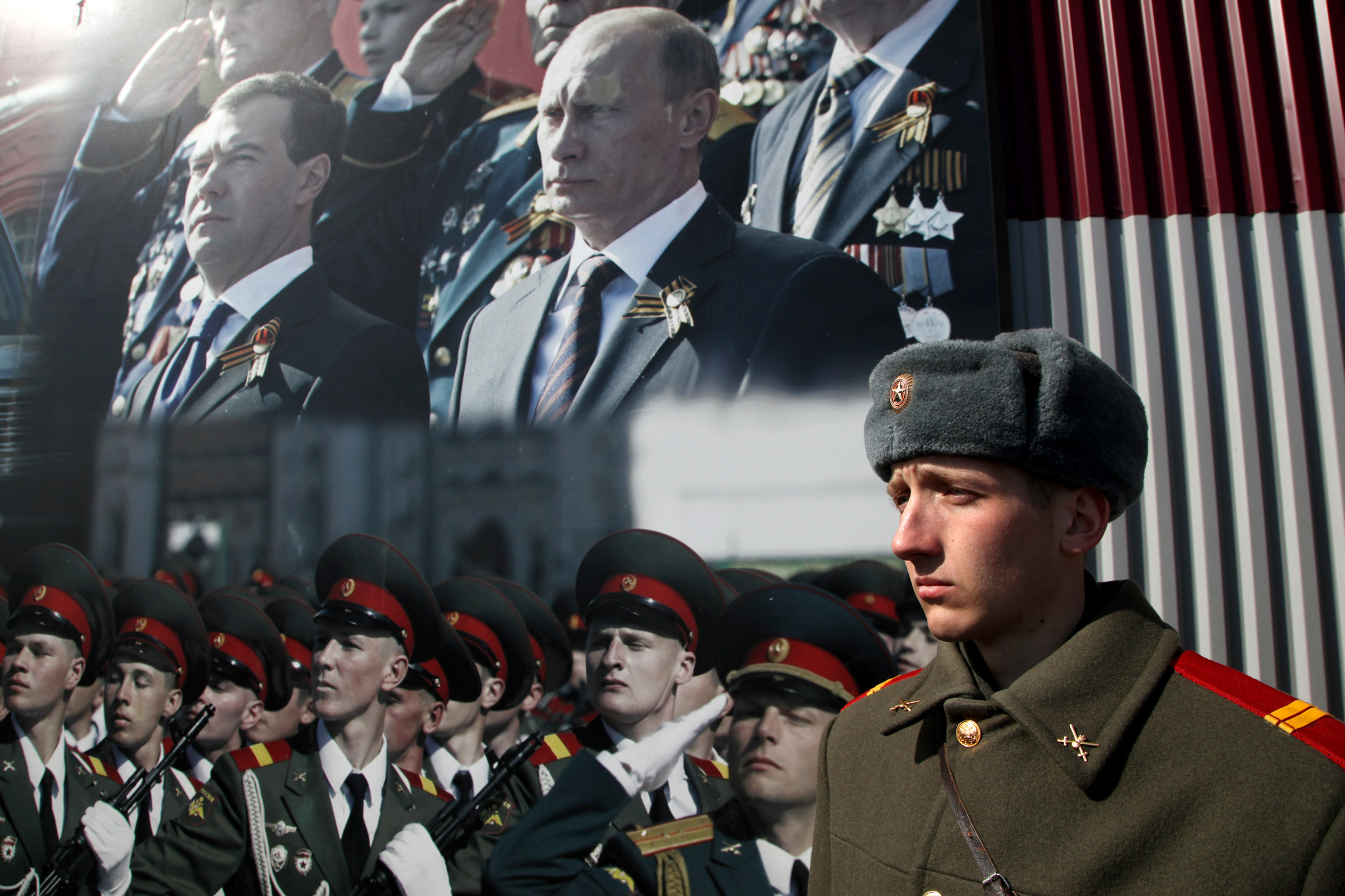 A Russian soldier stands in front of poster with portraits of Russian President-elect Vladimir Putin and outgoing President Dmitry Medvedev during a rehearsal for the Victory Day parade near Moscow on April 4, 2012. The parade is dedicated to the anniversary of the Soviet victory over Nazi Germany in World War II.
