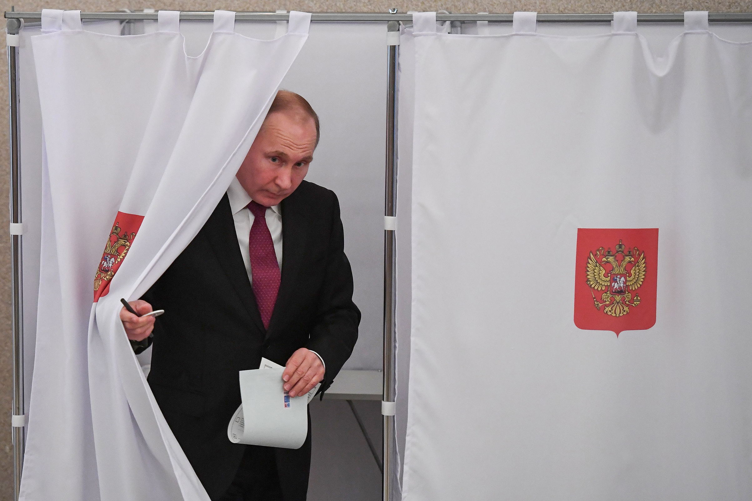 Russian President Vladimir Putin walks out of a voting booth at a polling station during the presidential election in Moscow on March 18, 2018.