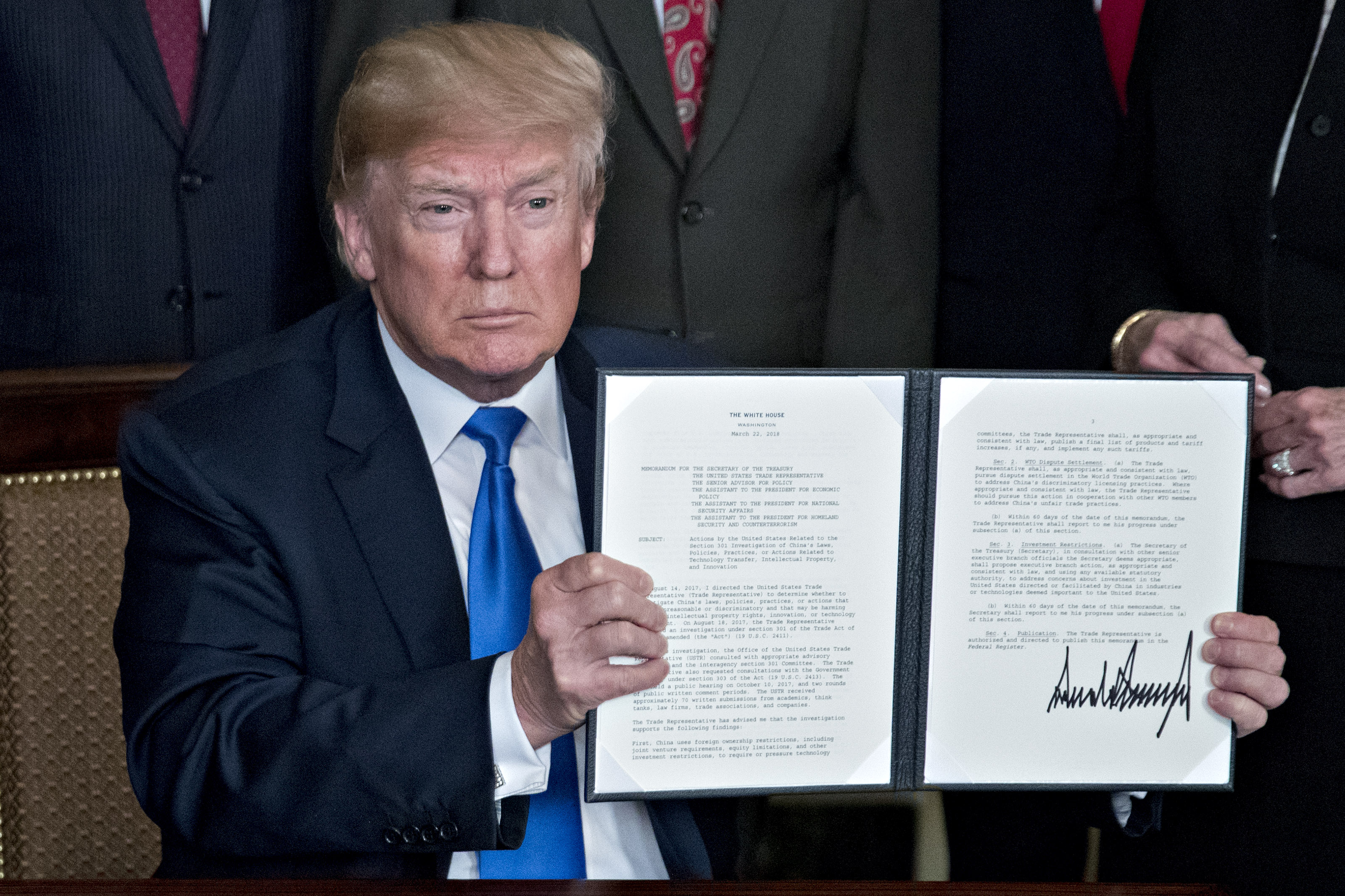 U.S. President Donald Trump holds up a signed presidential memorandum targeting China's economic aggression in the Diplomatic Room of the White House in Washington, D.C., U.S., on Thursday, March 22, 2018. Trump announced about $50 billion of tariffs against China over intellectual-property violations opening a new front in an escalating global trade skirmish that is shaking financial markets.