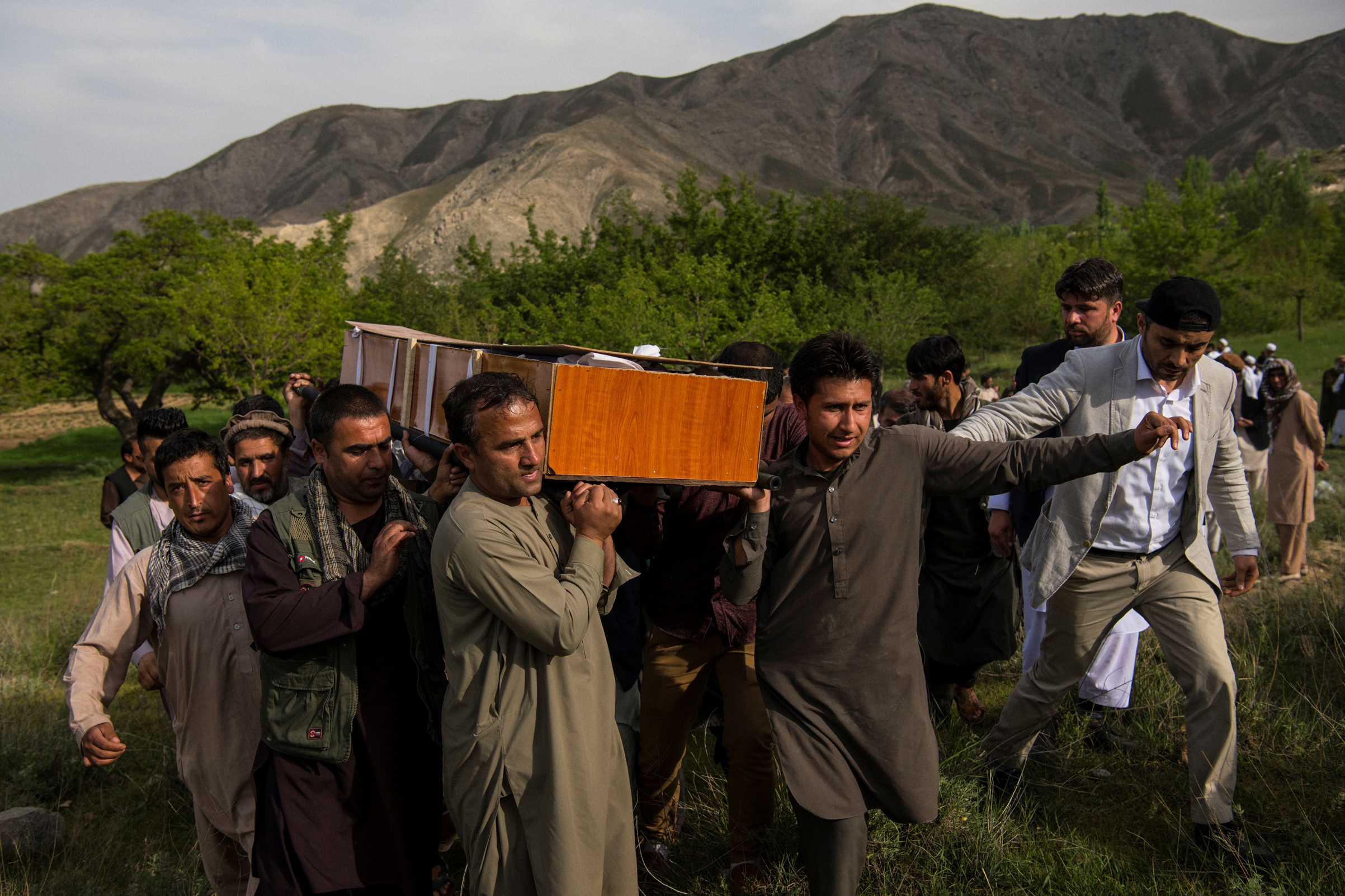 Relatives and friends of Agence France Presse Afghanistan Chief Photographer Shah Marai Faizi carry Marai's coffin before his burial in Gul Dara, Kabul, Afghanistan, on April 30, 2018.