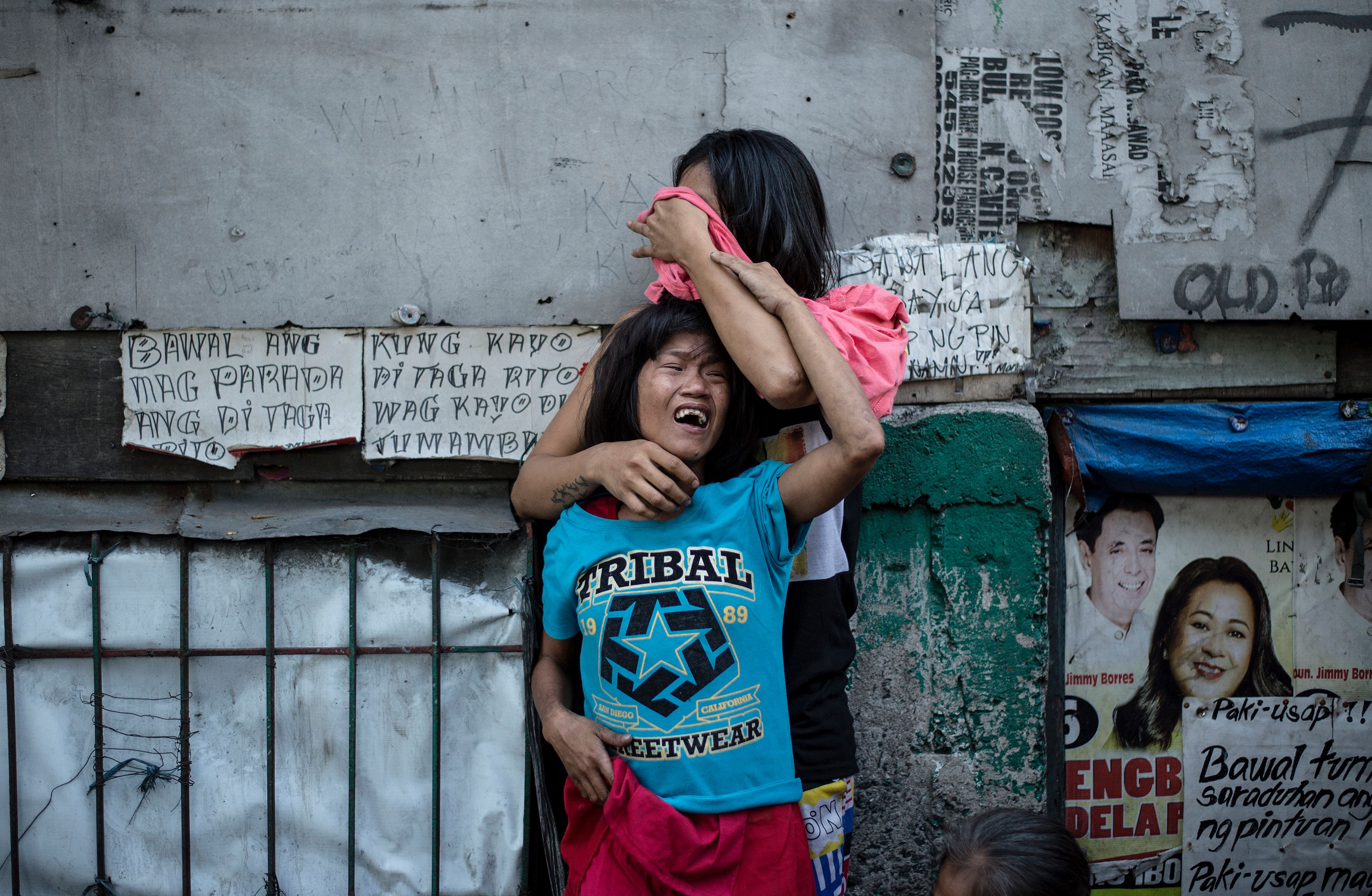 Analyn Roxas, 26, mourns with her sister after her partner, Valien Mendoza, a suspected drug dealer, was gunned down by unidentified assailants in Manila, March 7, 2017.