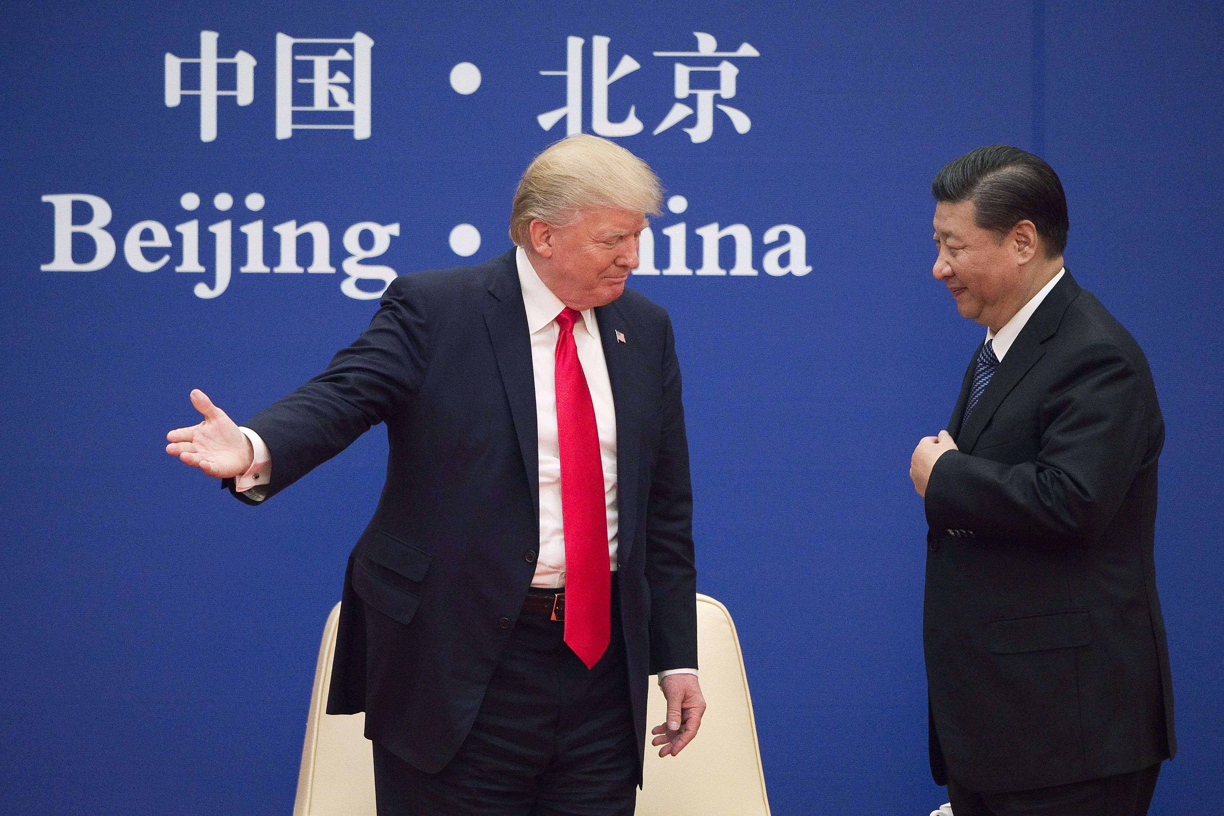 US President Donald Trump (L) gestures next to China's President Xi Jinping during a business leaders event at the Great Hall of the People in Beijing on November 9, 2017.
