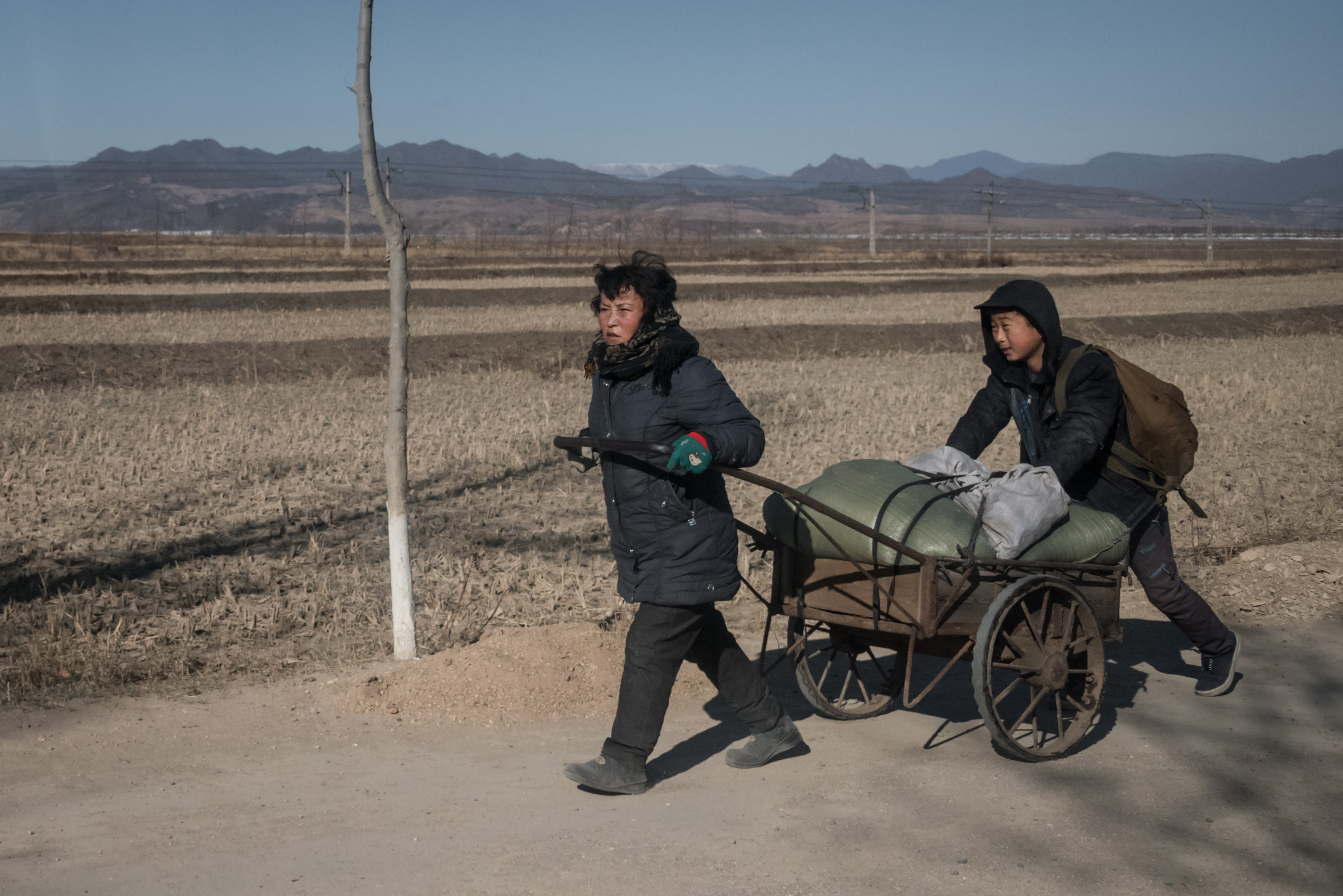 In a photo taken on Nov. 19, 2017, a woman and child pull a cart loaded with wood along a road near Kiliju on North Korea's northeast coast.