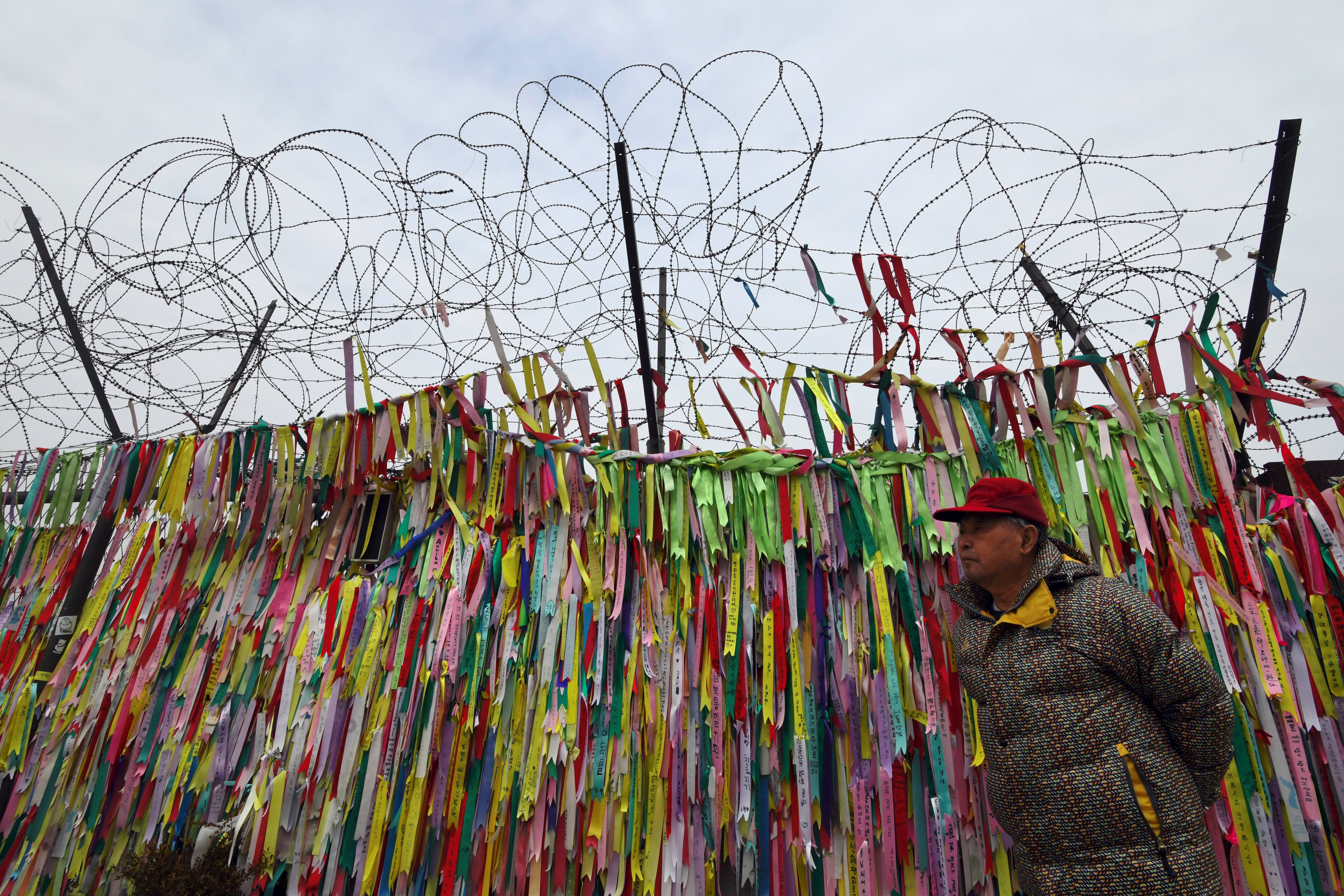 A man walks past a military fence covered with ribbons calling for peace and reunification at the Imjingak peace park near the Demilitarized Zone (DMZ) dividing the two Koreas at the border city of Paju on Jan. 8, 2018.