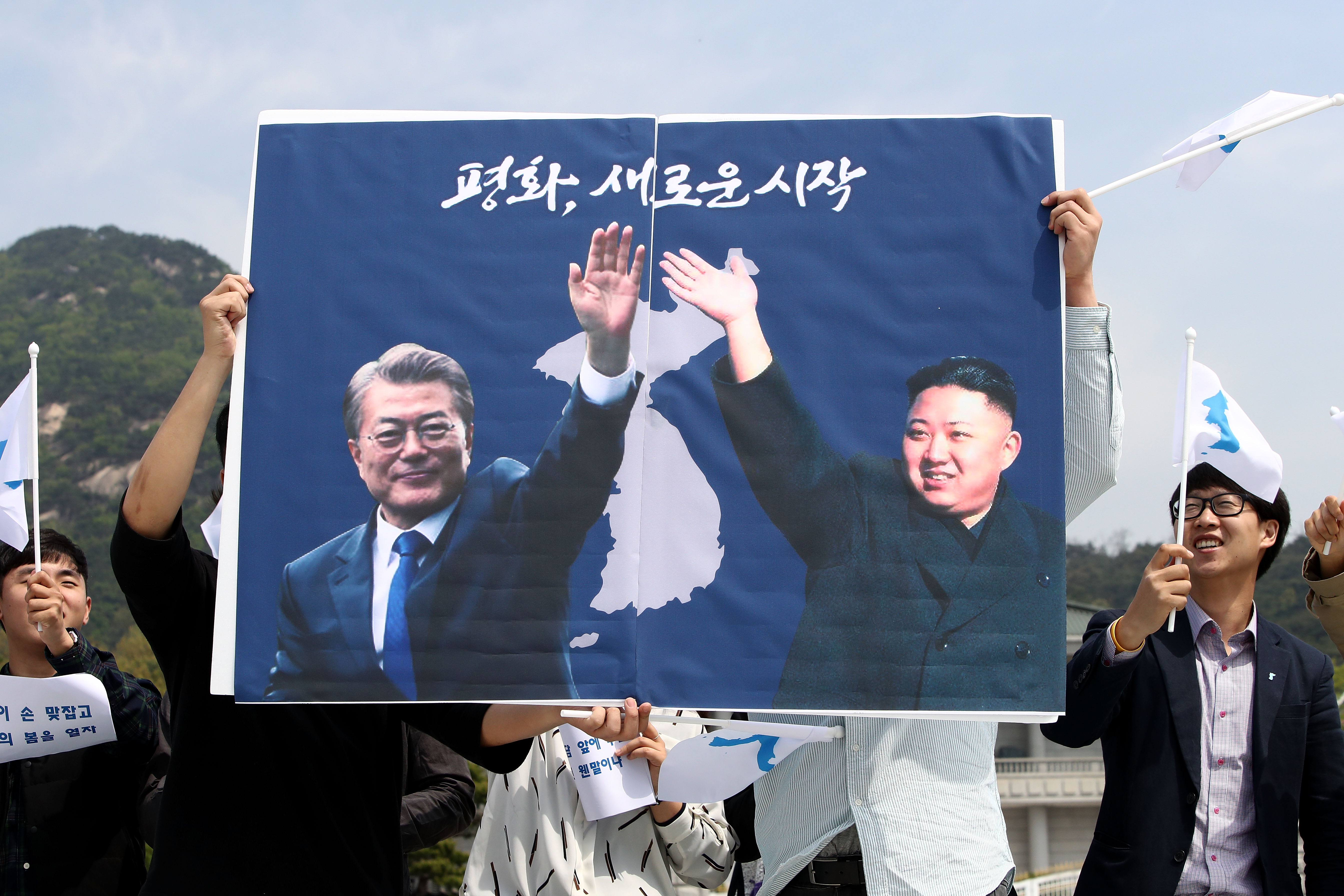 South Koreans hold up placards of South Korean President Moon Jae-In and North Korean leader Kim Jung-Un in front of Presidential Blue House  in Seoul, South Korea on April 26, 2018.