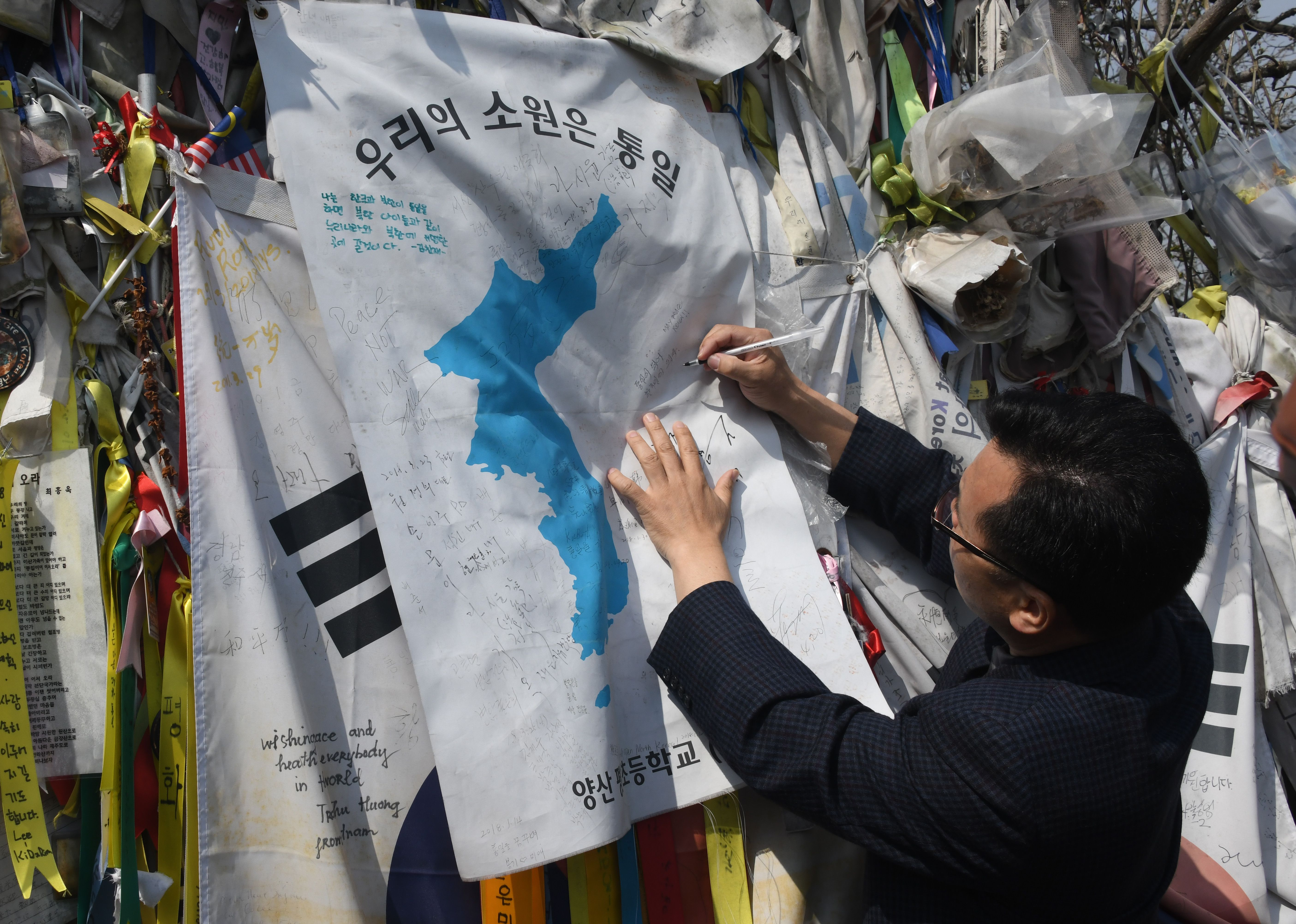 A man writes an inscription on a  Unification flag  hanging at a military fence at Imjingak peace park in Paju near the demilitarized zone dividing the two Koreas on April 26, 2018 ahead of the upcoming inter-Korea summit.