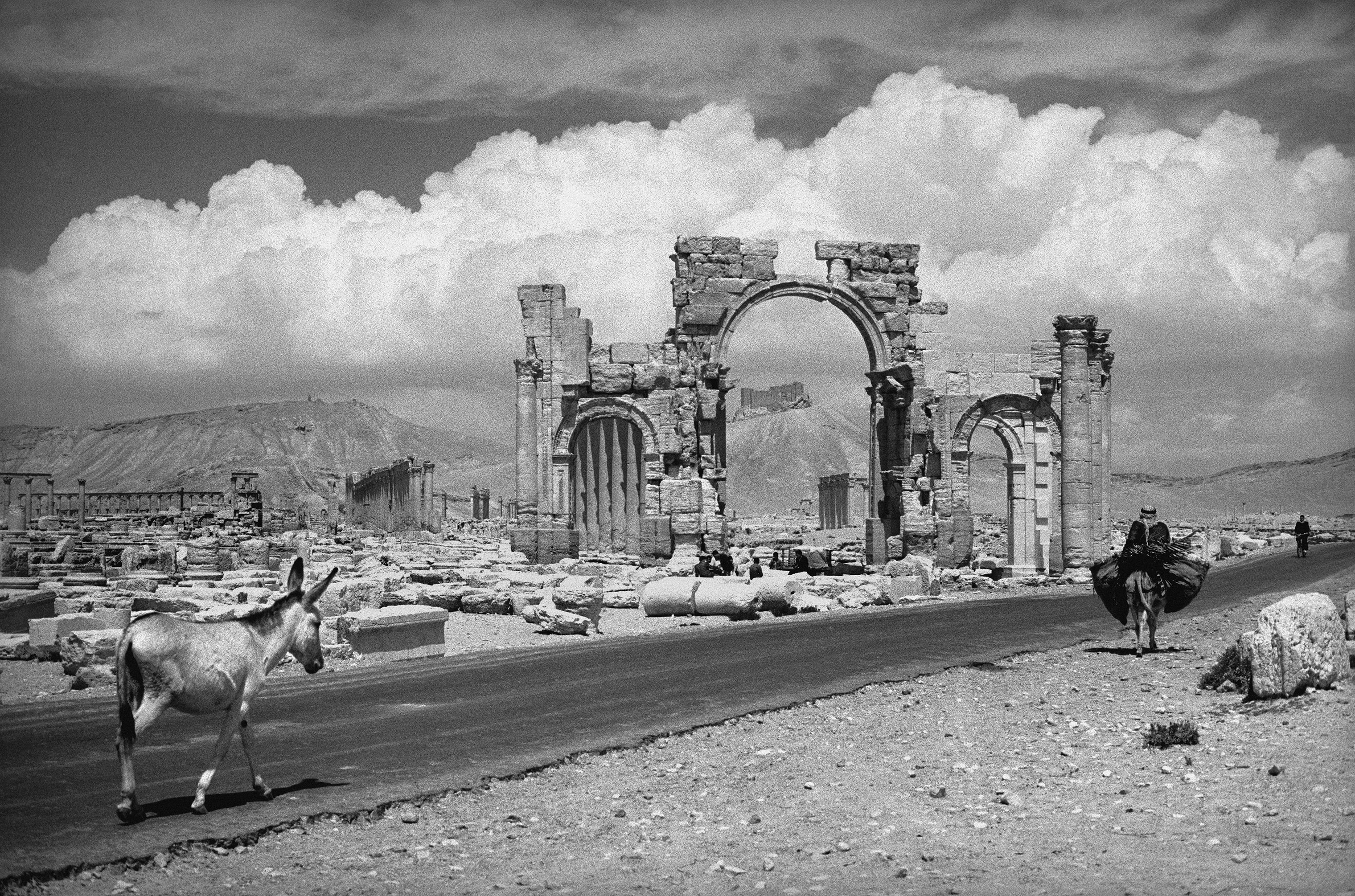General view of the ruins of Palmyra, Syria. A man on horse back passes as he would have done when Palmyra was originally a trading city in the first century AD. 1966.
