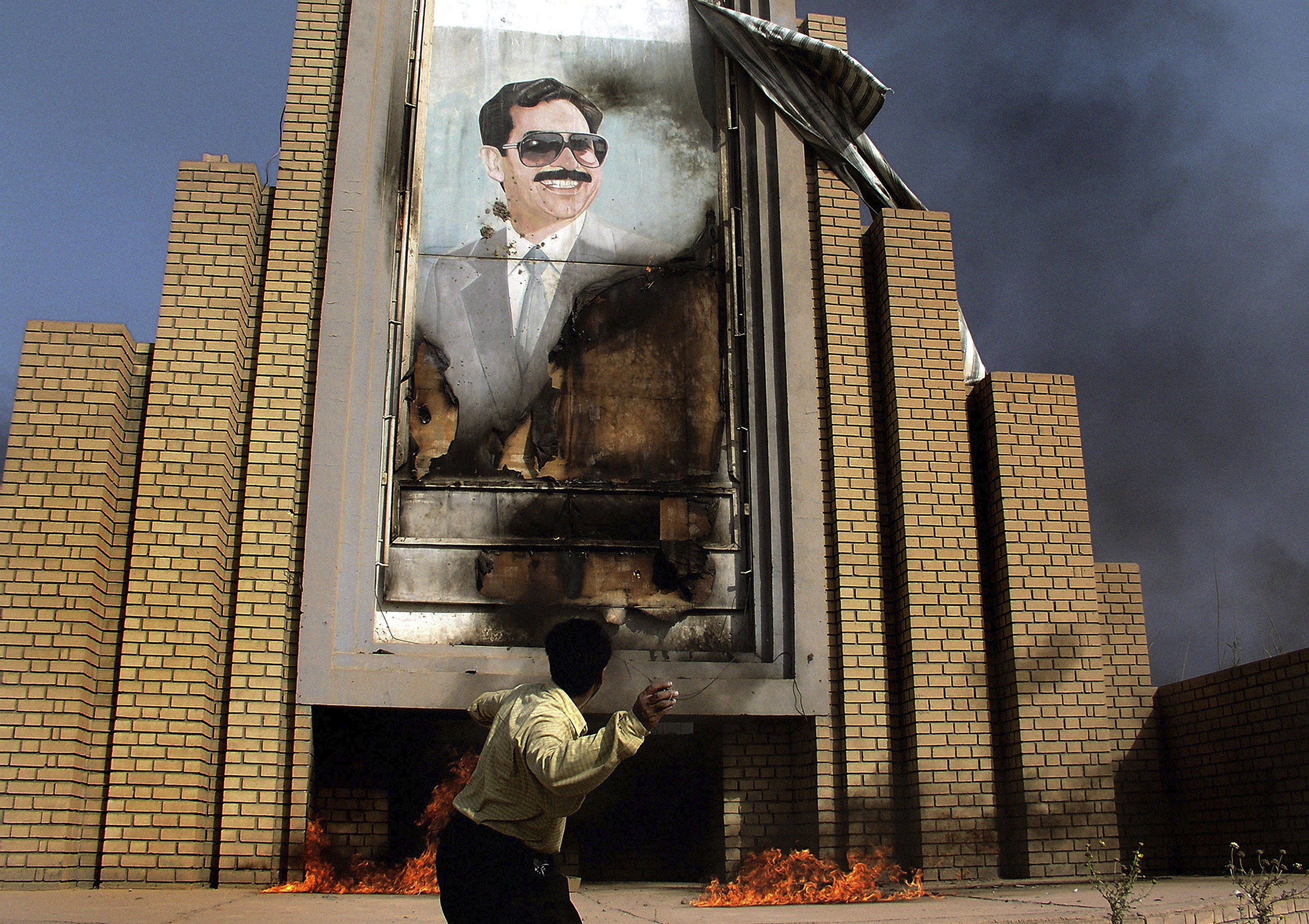 People burn and throw stones at a poster of Saddam Hussein in Baghdad, Iraq, on April 10, 2003.