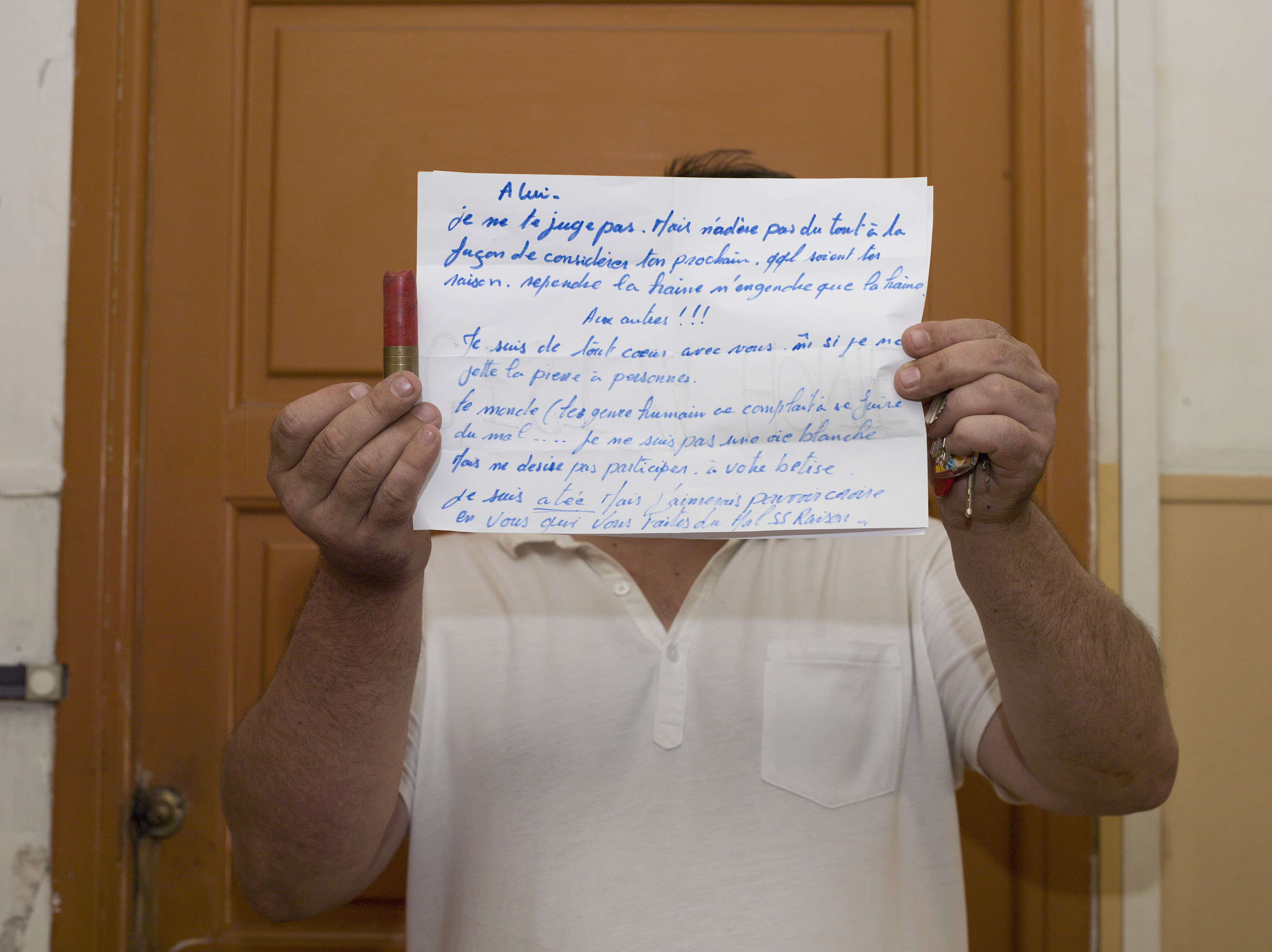 A neighbor, who didn't want to be identified holds a sign, in front of Mohamed Lahouaiej Bouhlel's doorway. Bouhlel was the driver of a truck that plowed into a crowd on the waterfront in Nice, France, killing 84 people. Holding a bullet shell from the police's forced entrance, he holds a sign that reads:  For him: I do not blame you. But I do not join you at all in the way you consider your neighbor. Regardless of your reason. Spilled hatred only begets hatred. For the others: I'm with you even if I do not throw stones on anybody. The world keeps hurting itself. I am not a white goose but I do not desire to participate in your foolishness.  2016.