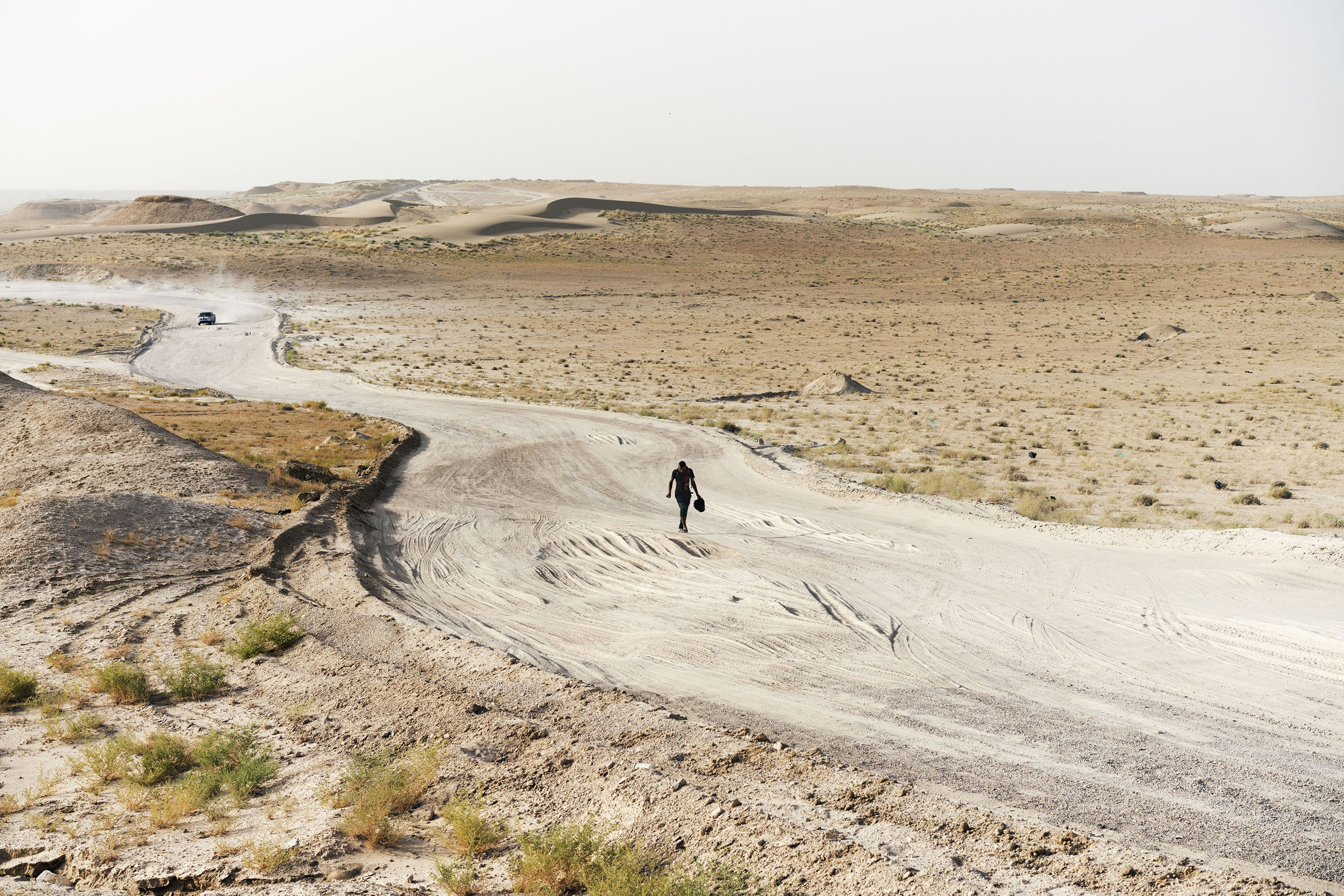 A man walks along a desert road near the town of Khalidiyah, in Iraq's Anbar Province, on July 12, 2016. The man, a native of Ramadi, was displaced when ISIS arrived in the city, and now lives with his family in a camp in the nearby town of Habbaniyah. Every day, he walks from Habbaniyah to Ramadi, where he works as a laborer clearing rubble from the war-torn streets.