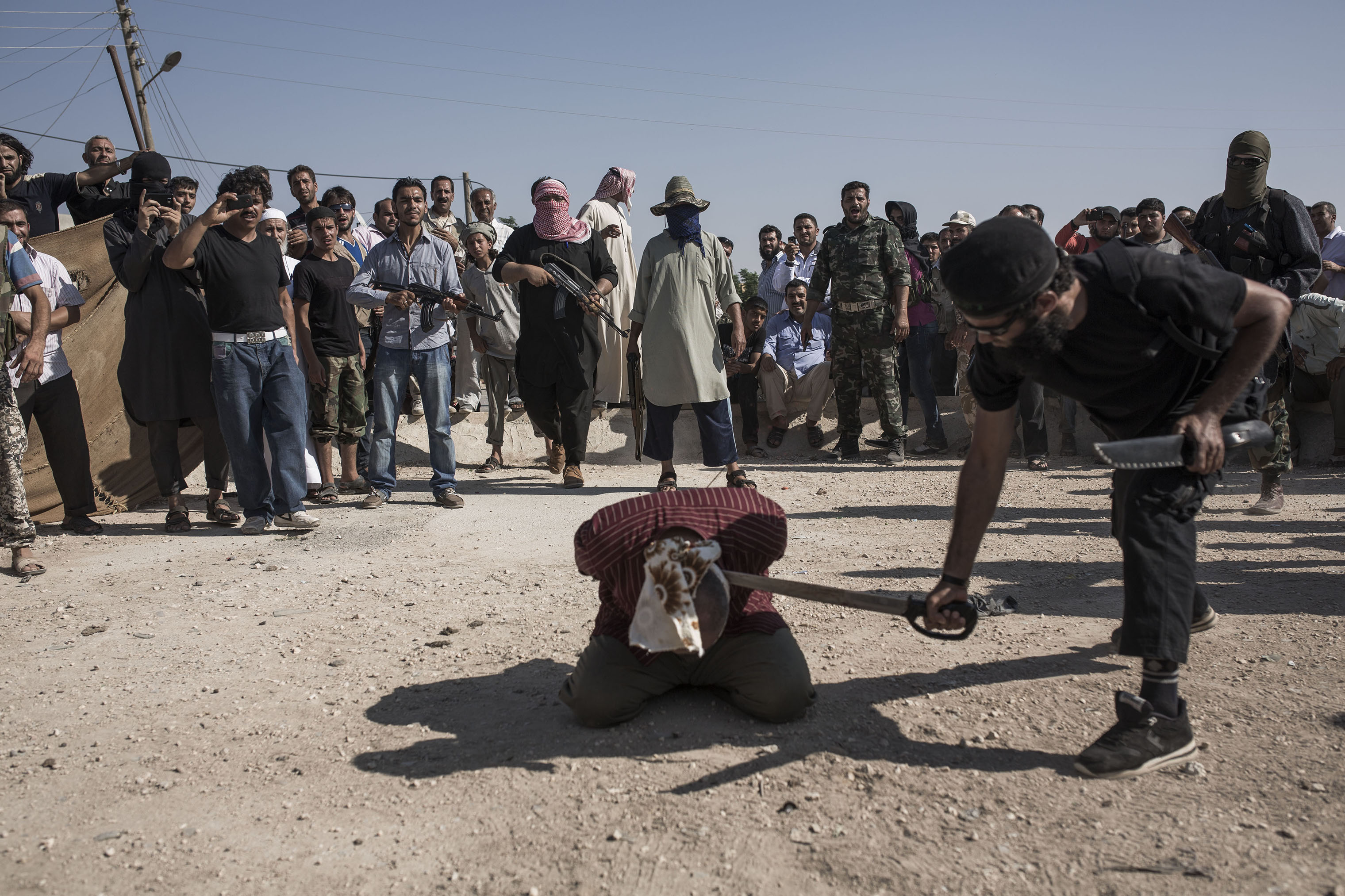A soldier from Assad's regime—charged with being an informant, murder, stealing and delivering 10 Free Syrian Army soldiers to the regime—is executed by ISIS in the town of Ehtemlat in northern Syria, 2013.