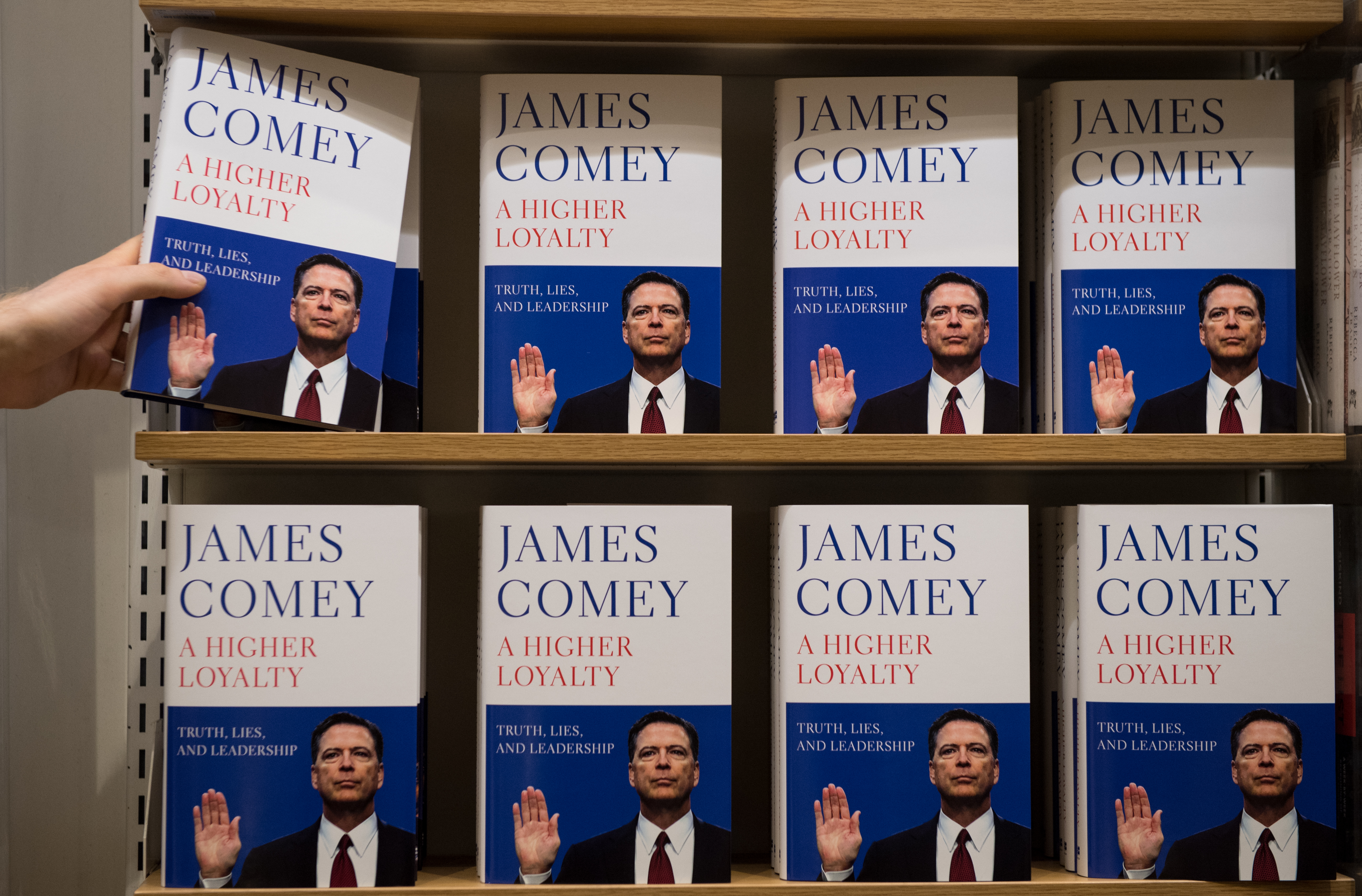 In this photo illustration a Waterstone's employee places copies of Former FBI Director James Comey's book on a shelf as it is released in the UK at Waterstone's, Piccadilly on April 17, 2018 in London, England.