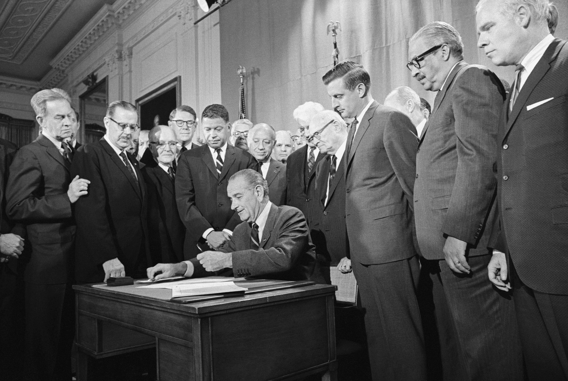 The Fair Housing Act's co-sponsors,  Democratic Senator from Minnesota Walter Mondale (third from right) and Republican Senator from Massachusetts Edward Brooke (fourth from the left in the striped tie), watch President Lyndon B. Johnson sign the civil rights bill into law on April 11, 1968.