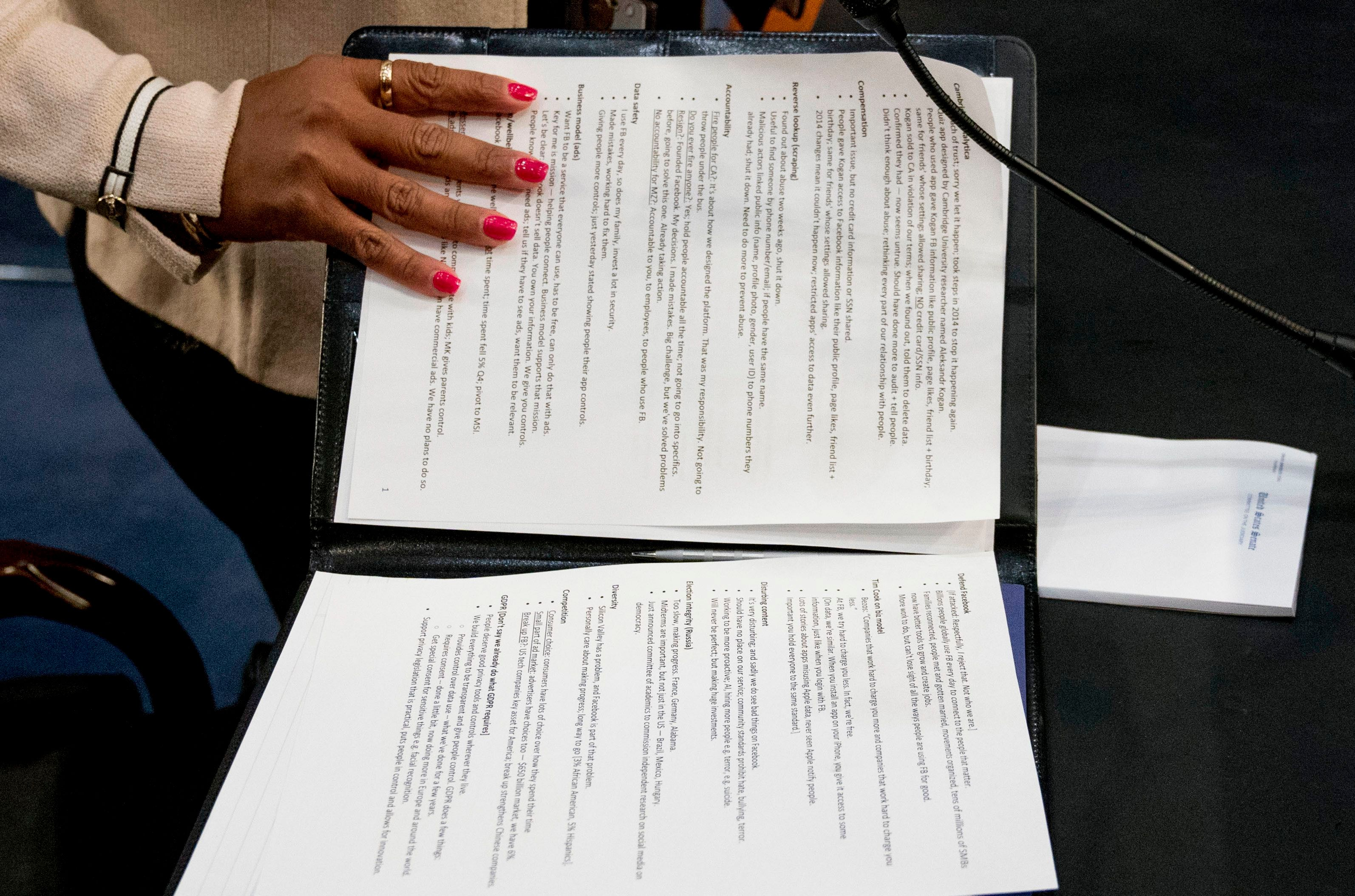 An aide to Facebook CEO Mark Zuckerberg closes a binder of notes left on the table as Zuckerberg takes a short break from testifying before a joint hearing of the Commerce and Judiciary Committees on Capitol Hill in Washington, about the use of Facebook data to target American voters in the 2016 election Facebook Privacy Scandal Congress.