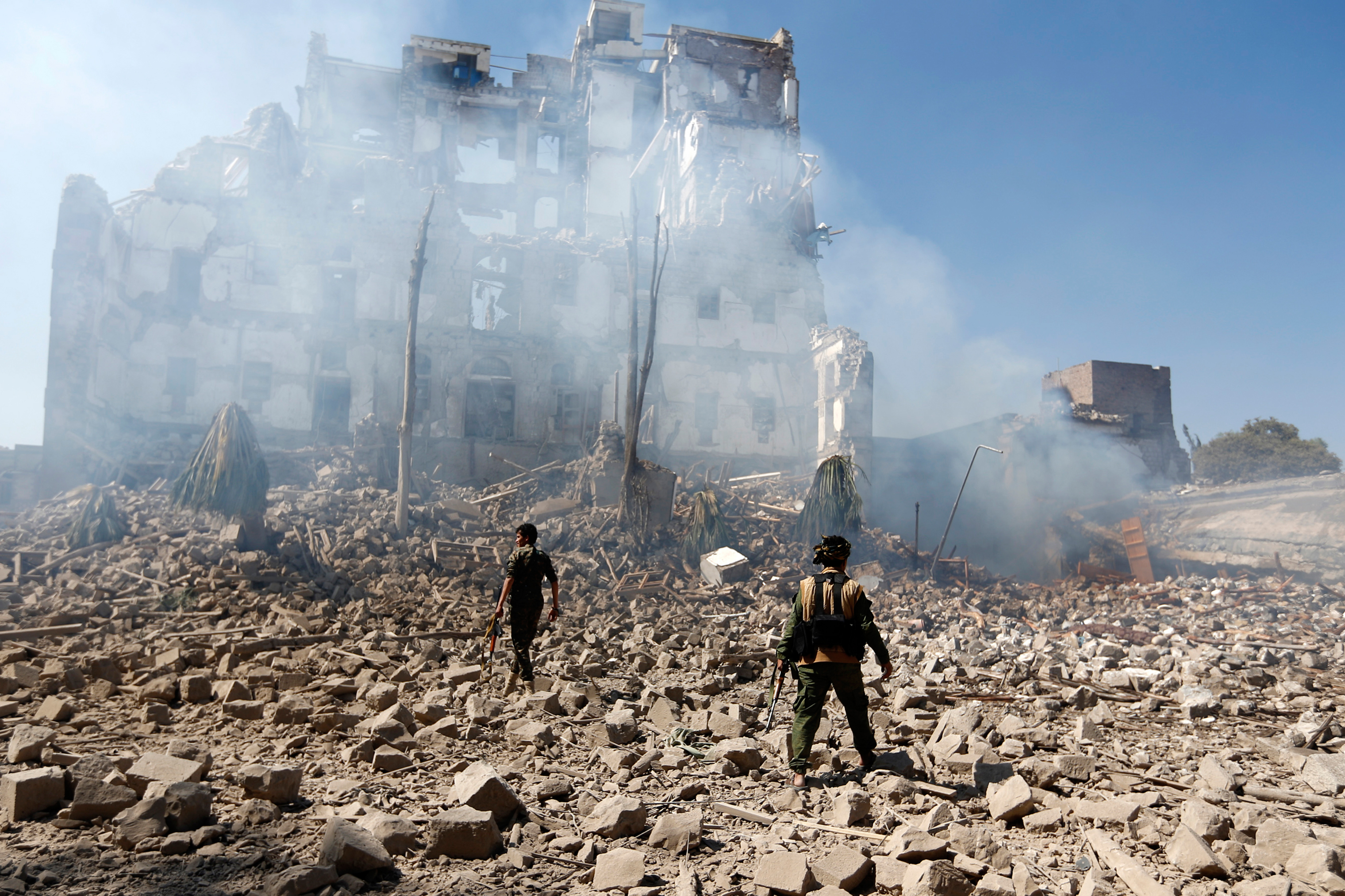 Houthi fighters inspect the site of a reported airstrike by the Saudi-led coalition that targeted Yemen's presidential palace in Sana'a on Dec. 5